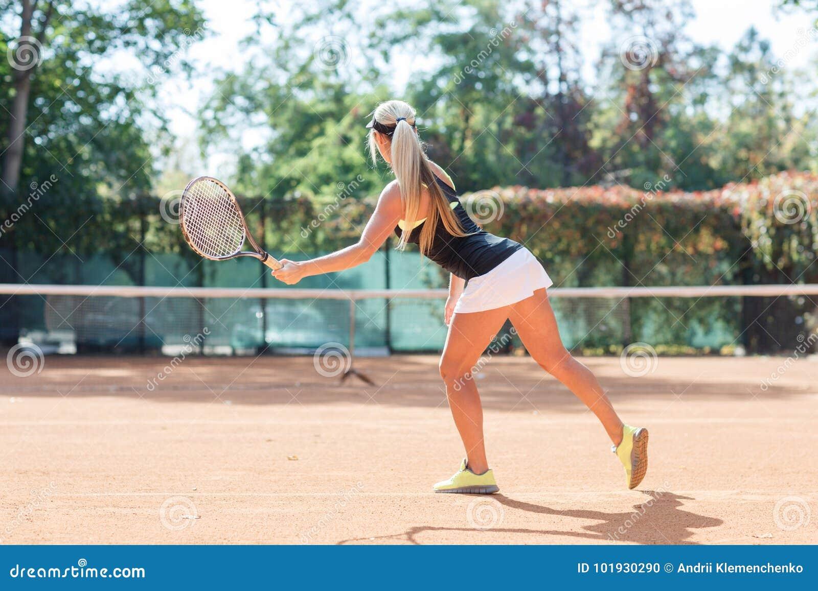 De jonge Kaukasische blondevrouw speelt tennis openlucht Mening van rug De speler van het tennis in actie Horizontaal beeld