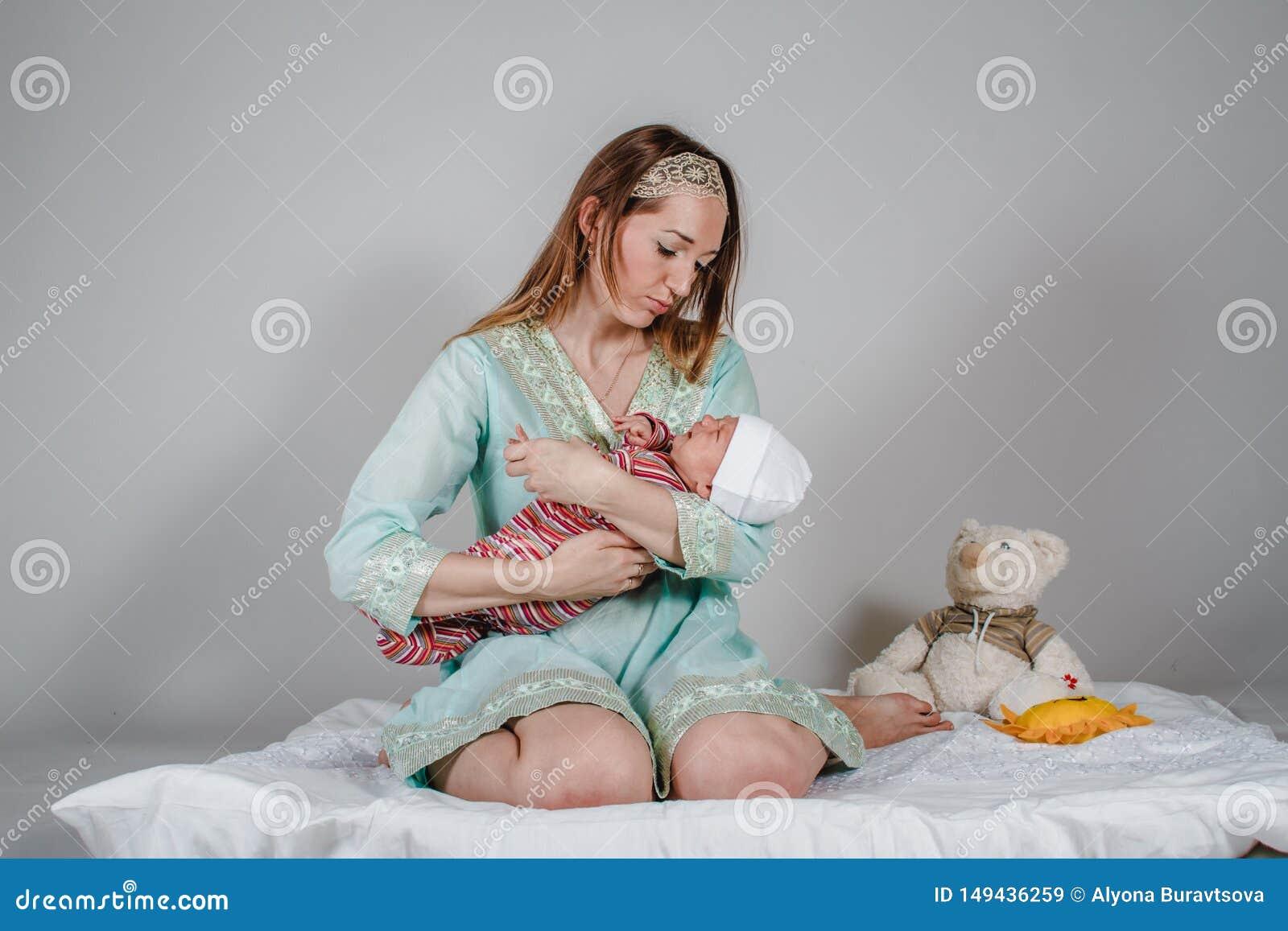 De jonge Kaukasische vrouw kalmeert een pasgeboren baby