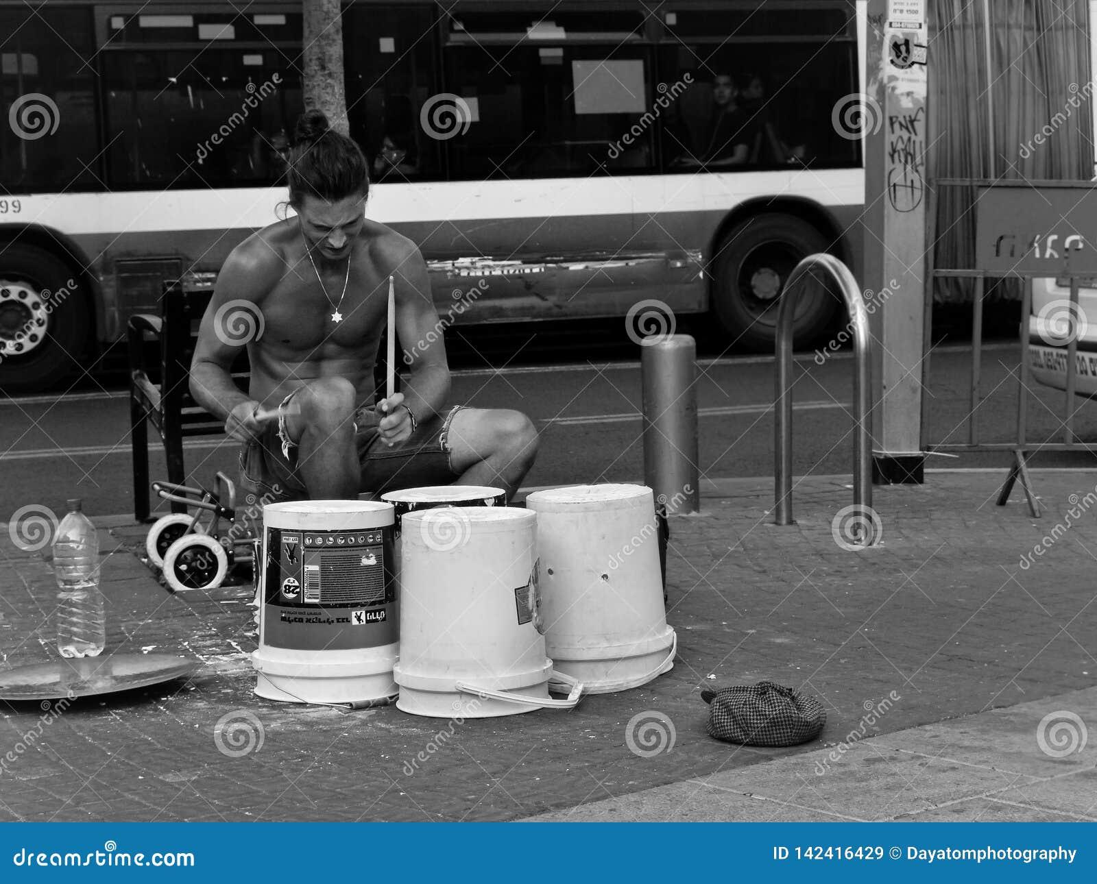 De jonge knappe straatmusicus, het spelen trommelt op containerdozen in het stedelijke plaatsen voor een bus