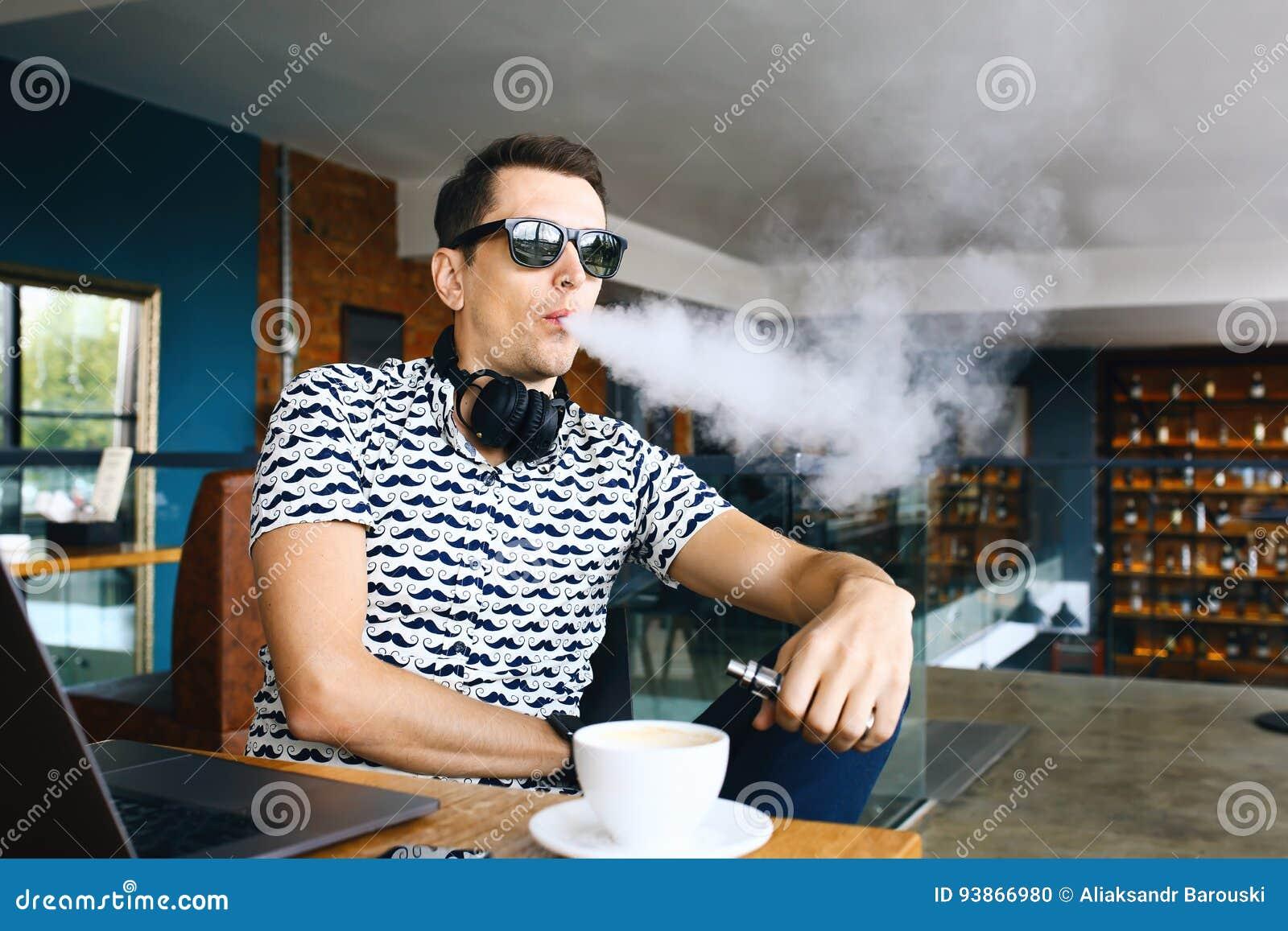 De jonge knappe zitting van de hipstermens insunglasse in koffie met een kop koffie, het vaping en versies een wolk van damp