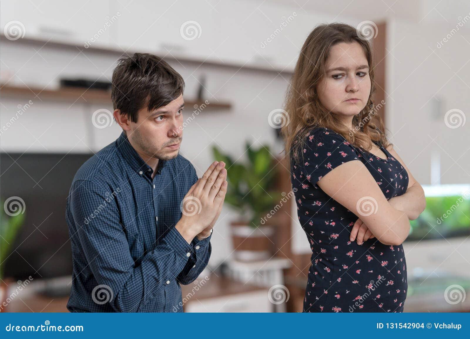De jonge man bedelt thuis voor vergiffenis jonge boze vrouw