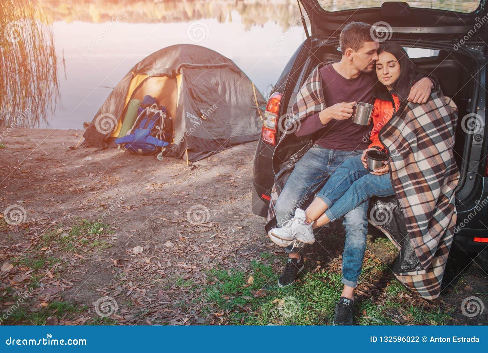 De jonge man omhelst vrouw Zij zitten in boomstam Het model is behandeld met deken Het paar is bij meer Er is tent bij waterlijn