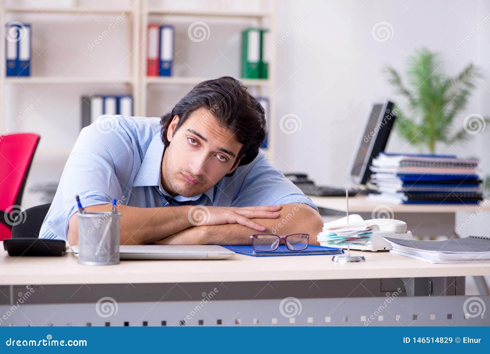 De jonge mannelijke zakenmanwerknemer ongelukkig met het bovenmatige werk