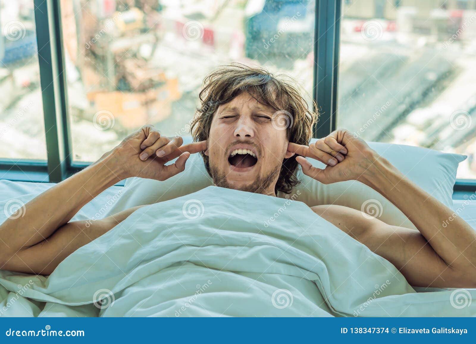 De jonge mens die op een bed liggen behandelde haar oren wegens het lawaai In het venster na het bed kunt u de bouw zien