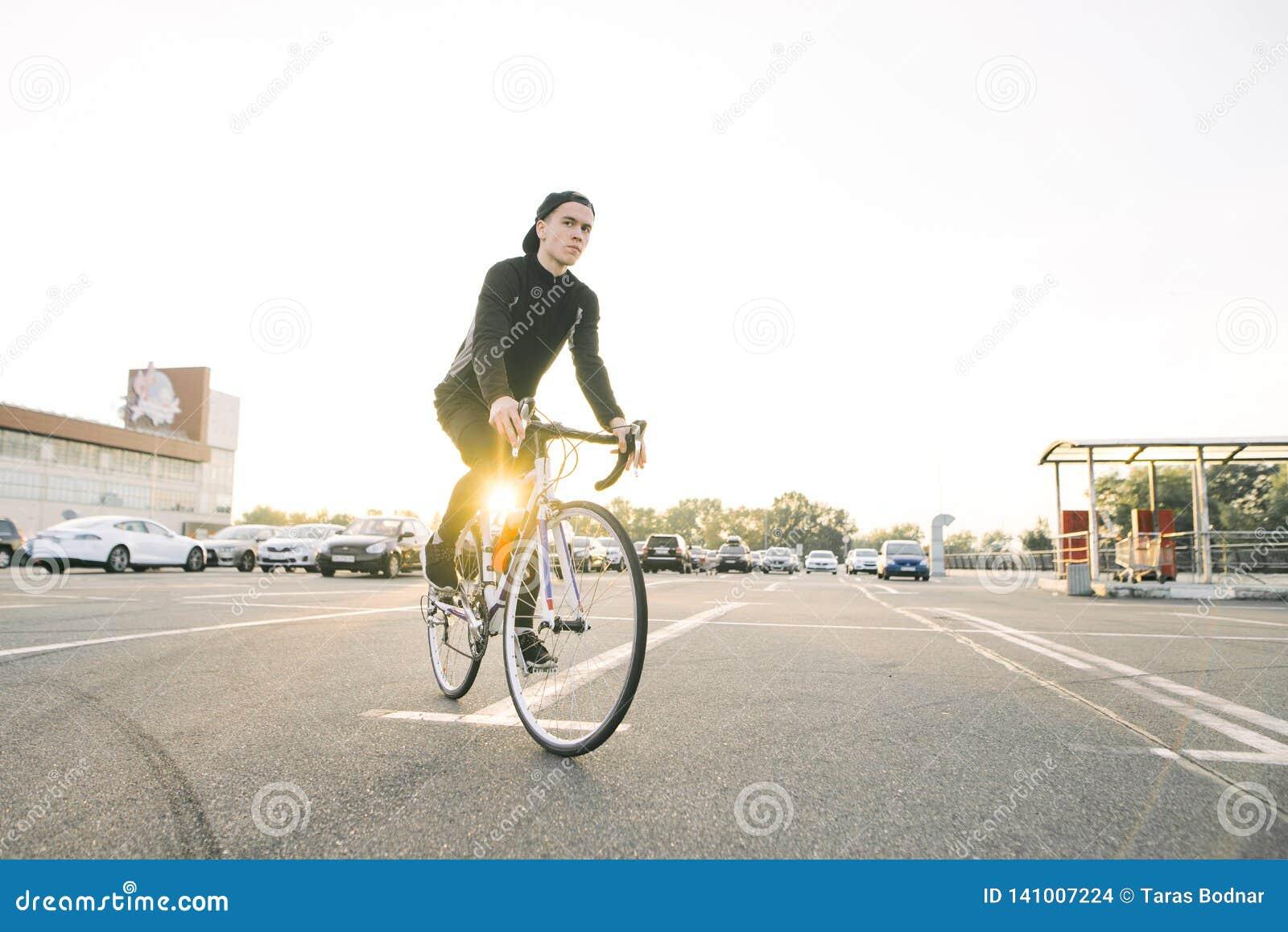 De jonge mens in donkere sportkleding en een GLB draagt een witte fiets in het parkeerterrein in de zon