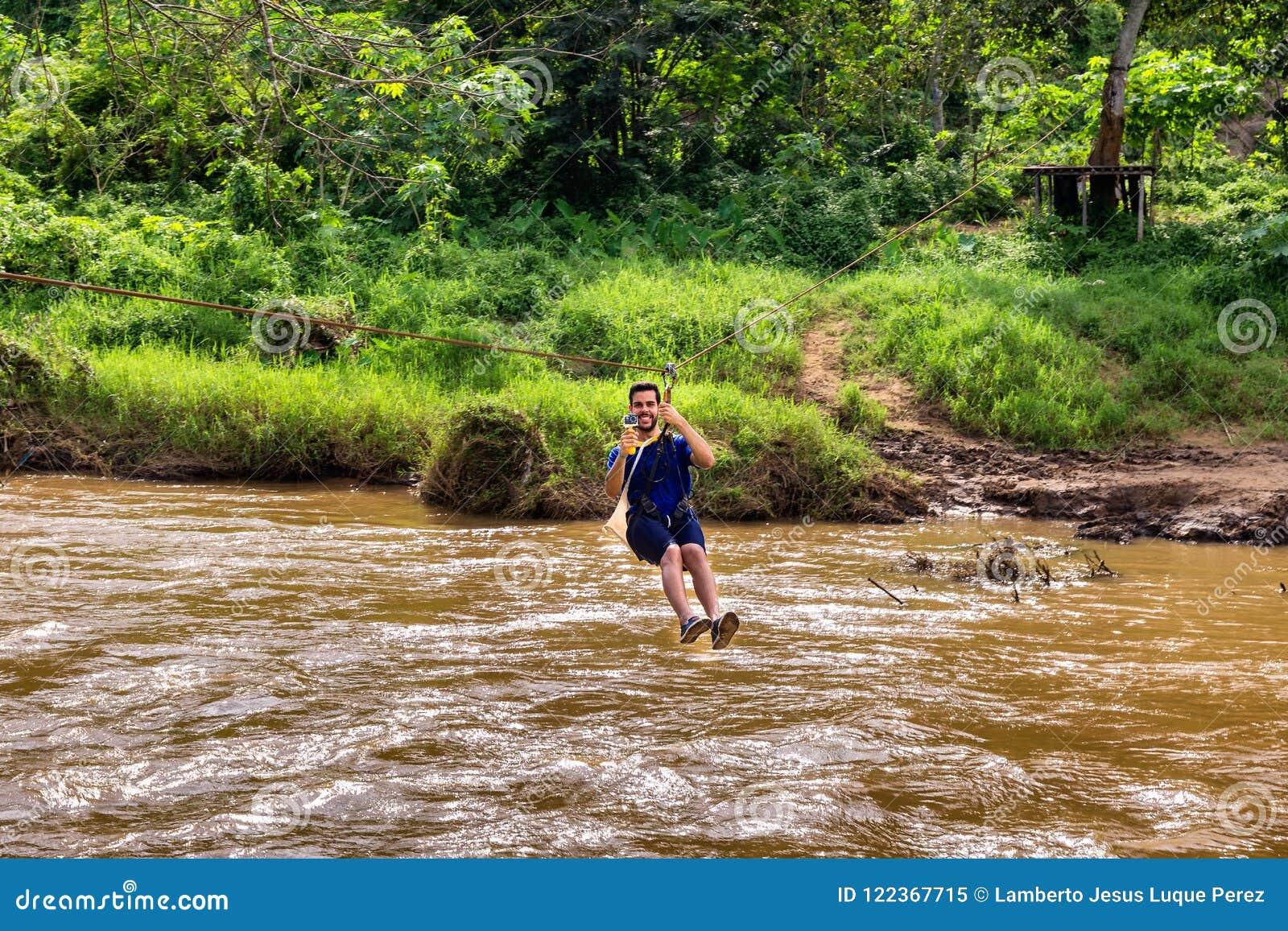 De jonge mens gaat door een rivier op pitlijn in Chiang Mai in Thai