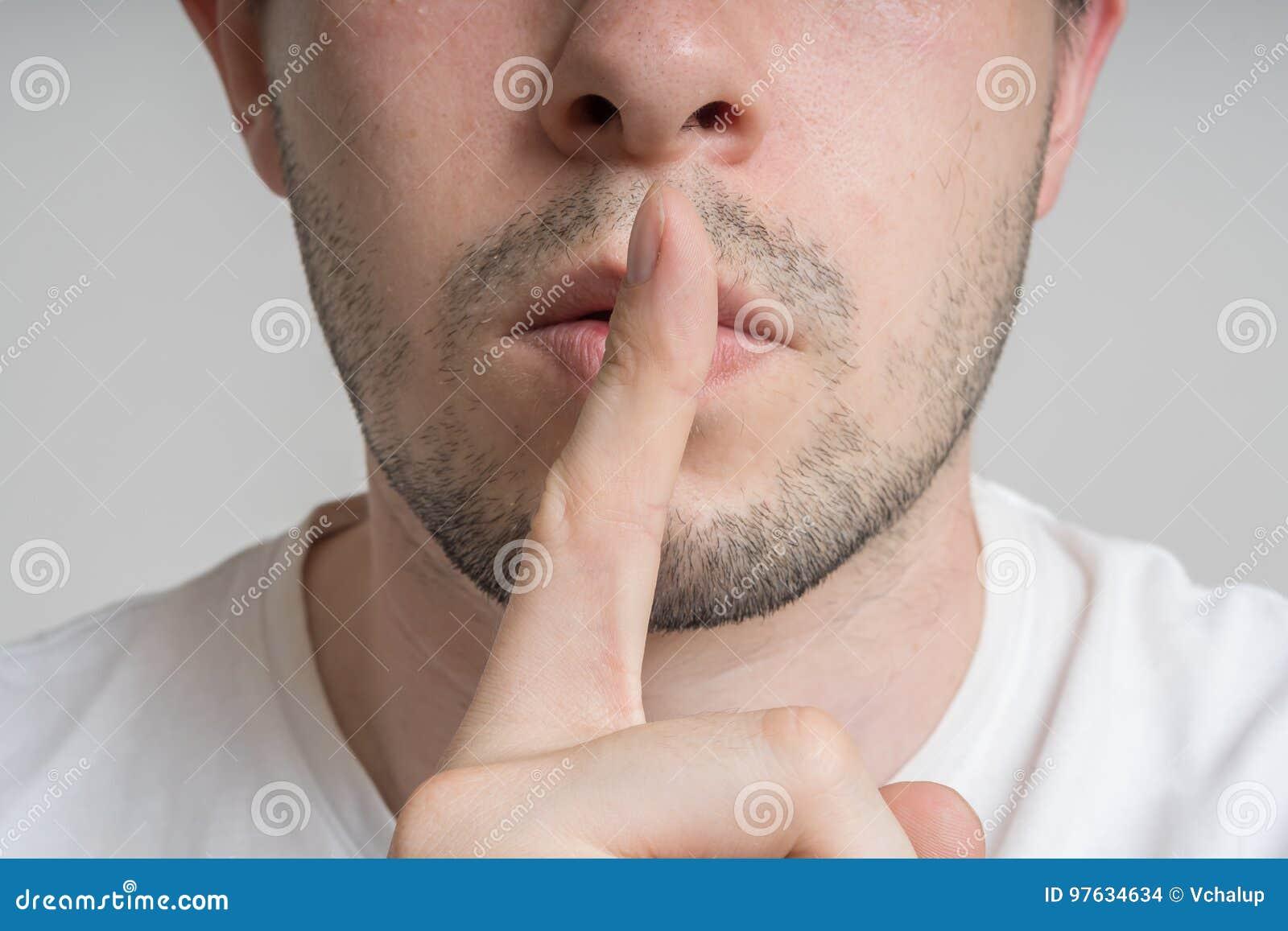 De jonge mens heeft vinger op lippen en het tonen stil gebaar zijn