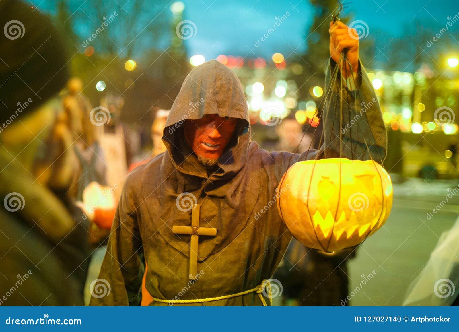 De jonge mens kleedde zich als monnik die gebogen pompoen dragen aan Halloween