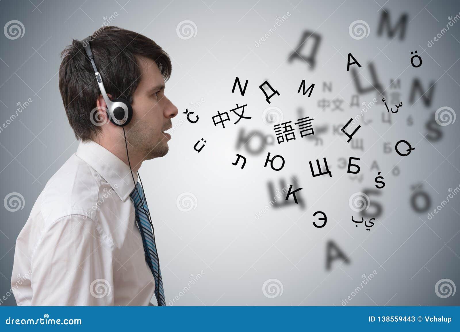 De jonge mens met hoofdtelefoons leert verschillende vreemde talen