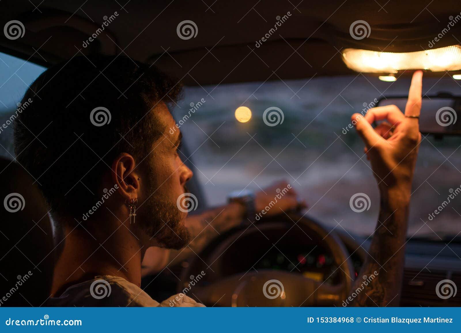 De jonge mens met oorringen drijft een auto bij nacht