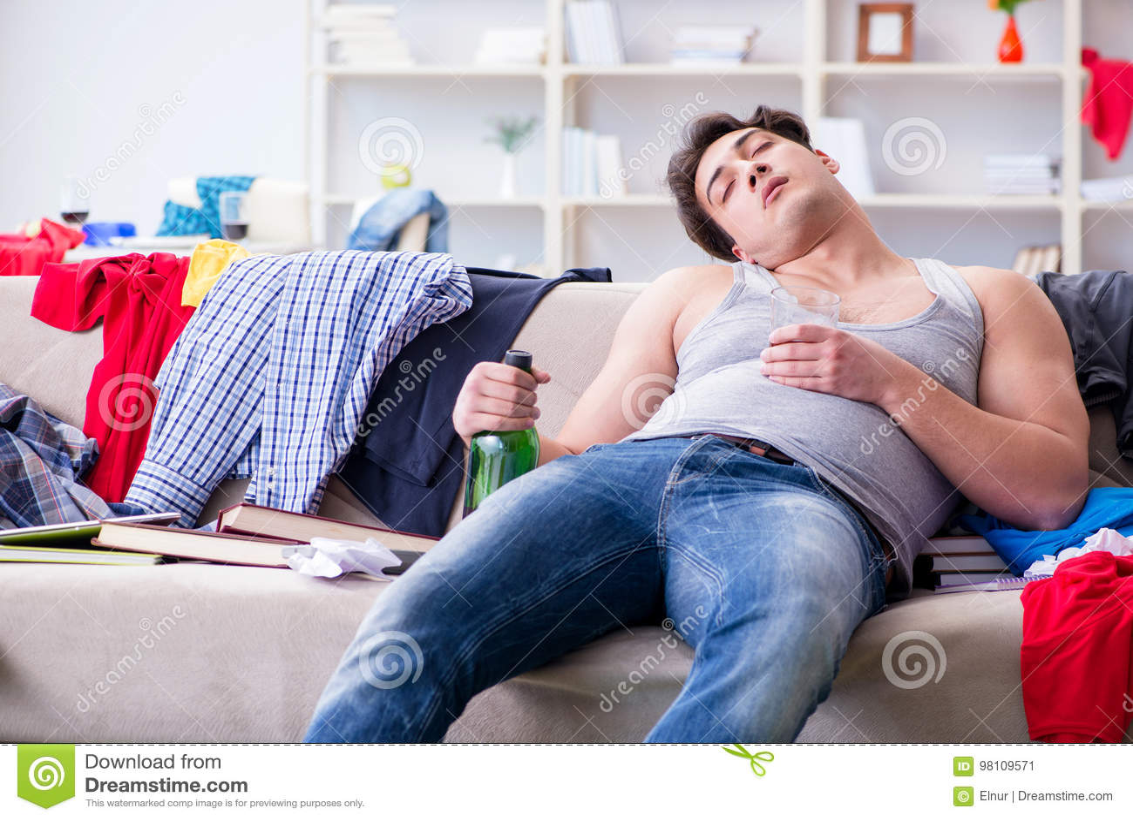 De jonge mens student gedronken het drinken alcohol in een slordige ruimte