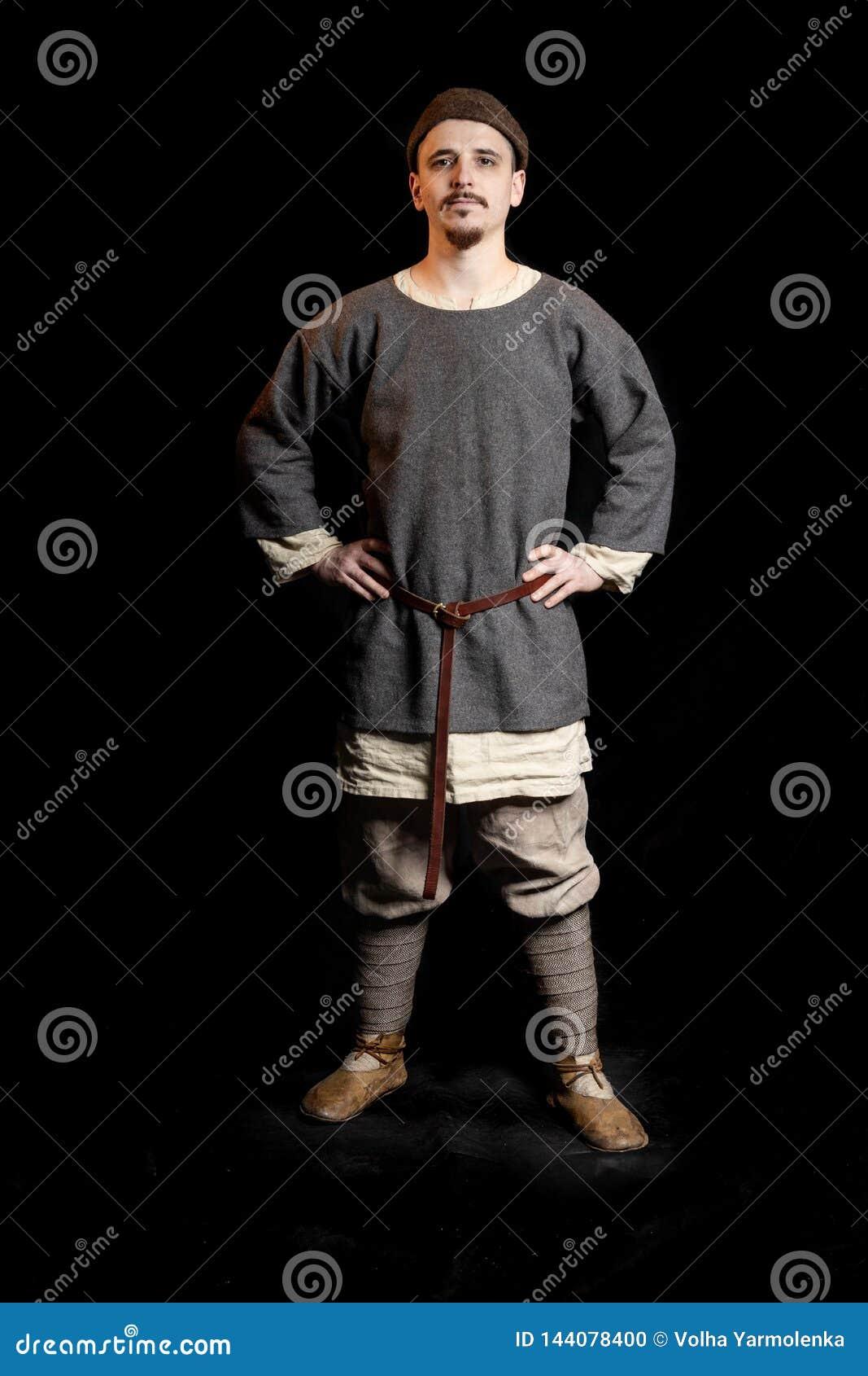 De jonge mens in toevallige grijze kleren en een hoed van Viking Age kijkt ernstig, overhandigt op heupen