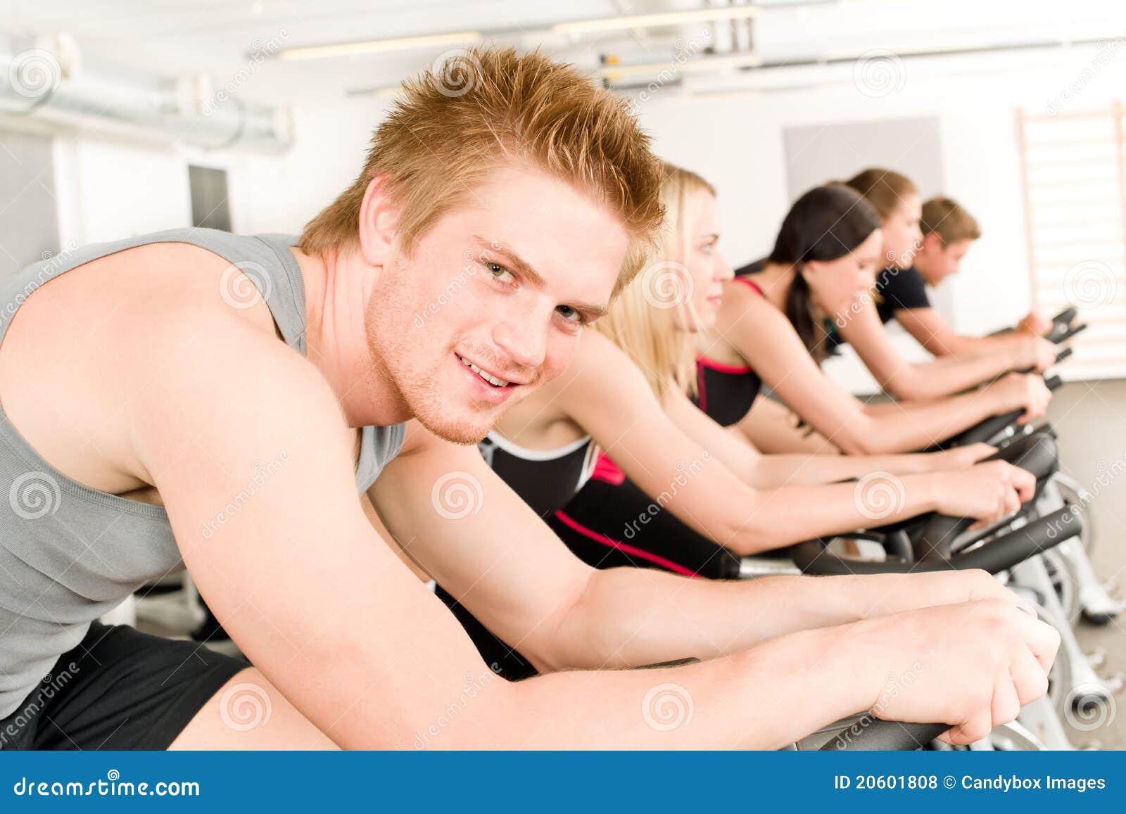De jonge mens van de geschiktheid bij gymnastiekfiets het spinnen
