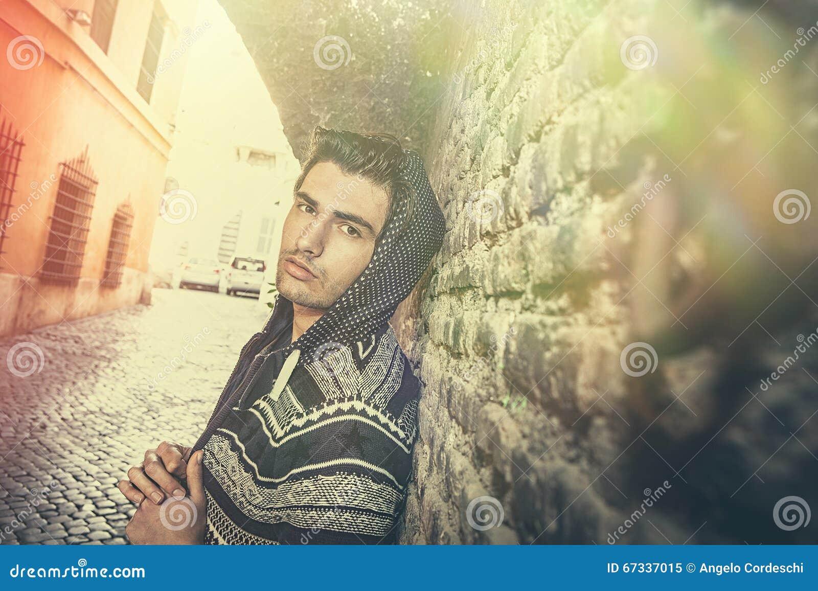 De jonge mens van de straatstad het model kijken, oude stedelijke muur