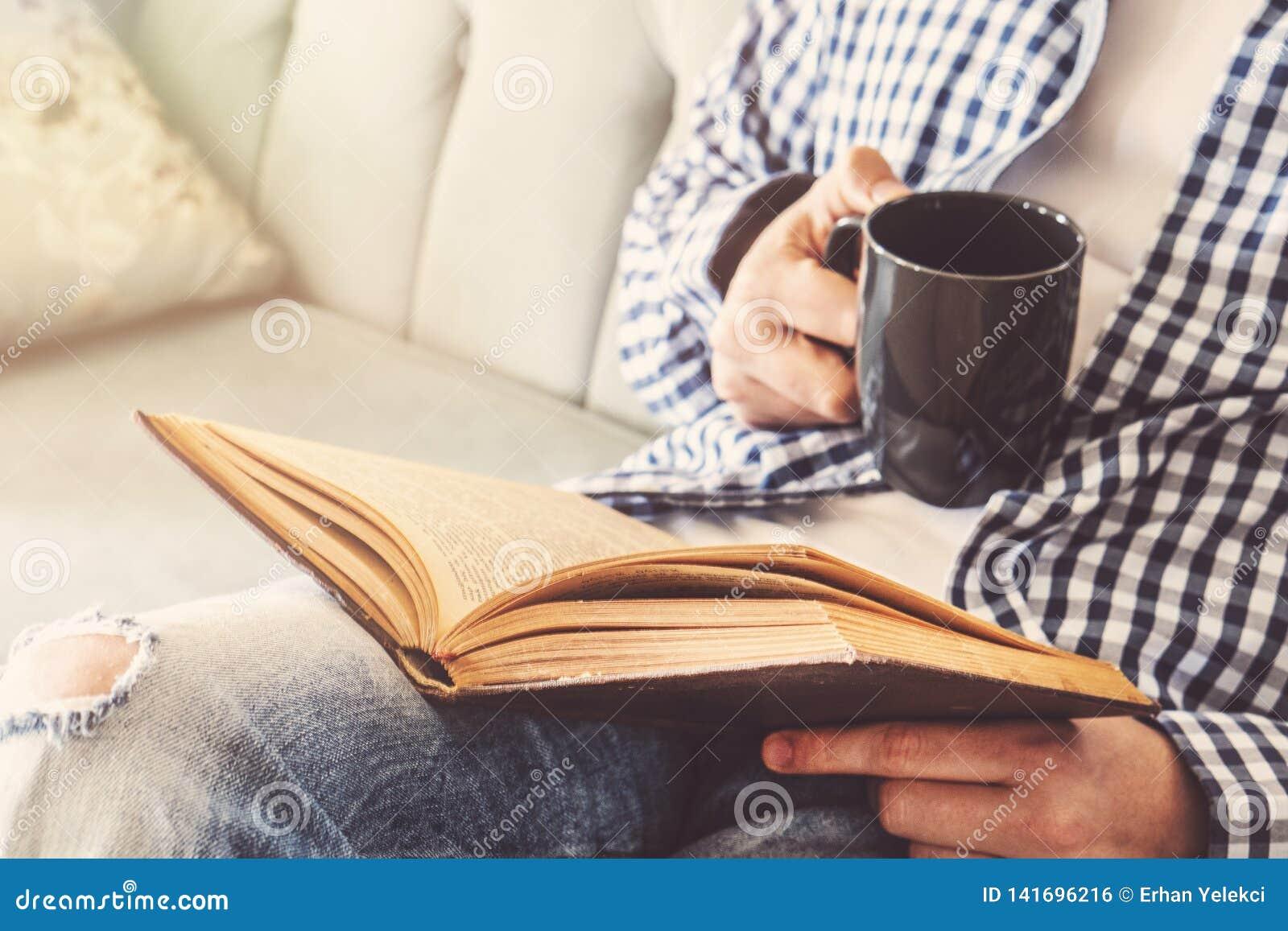 De jonge mens zit op een bank en leest een boek terwijl het houden van een kop van koffie of thee