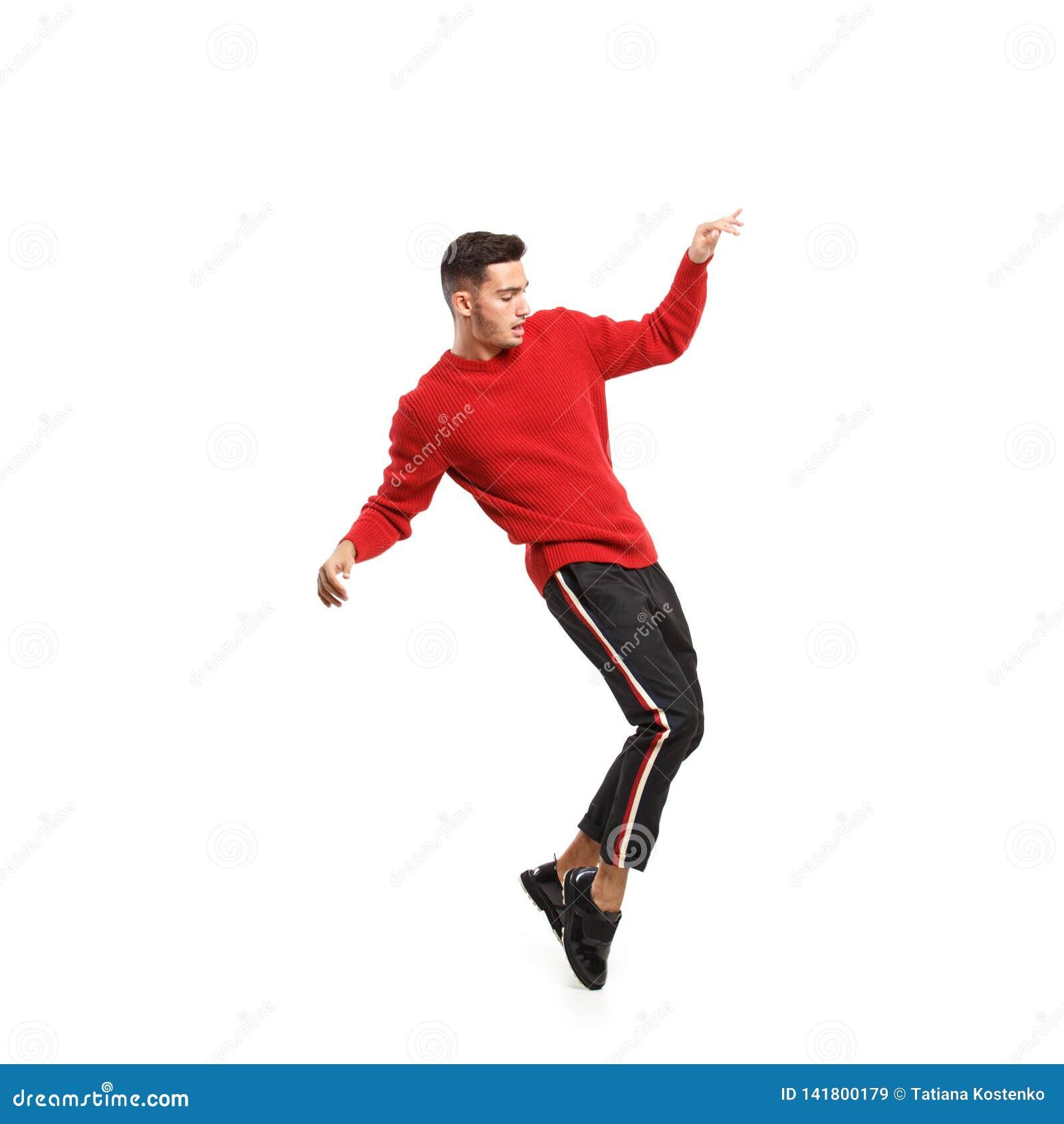 De jonge modieuze mens kleedde zich in rode col en donkere broek met strepen op de kantendansen op de witte achtergrond in