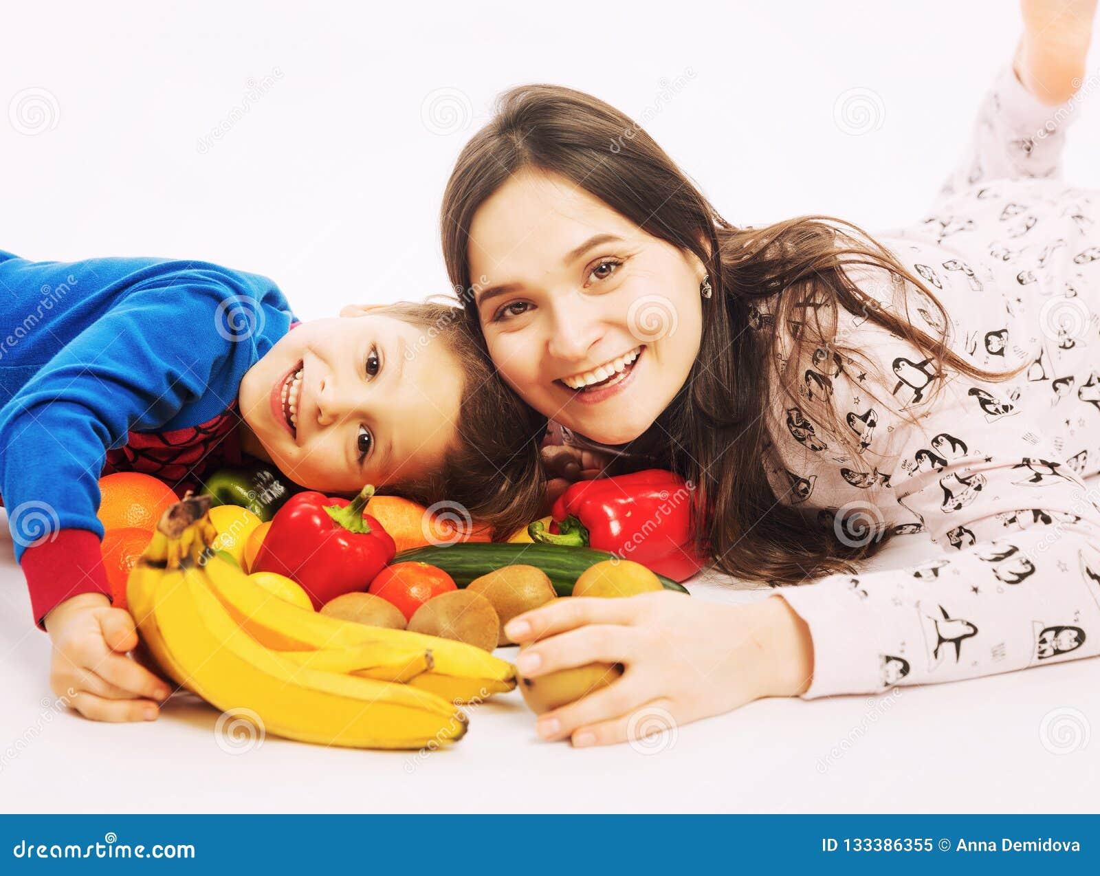 De jonge moeder eet fruit en groenten met haar jonge zoon