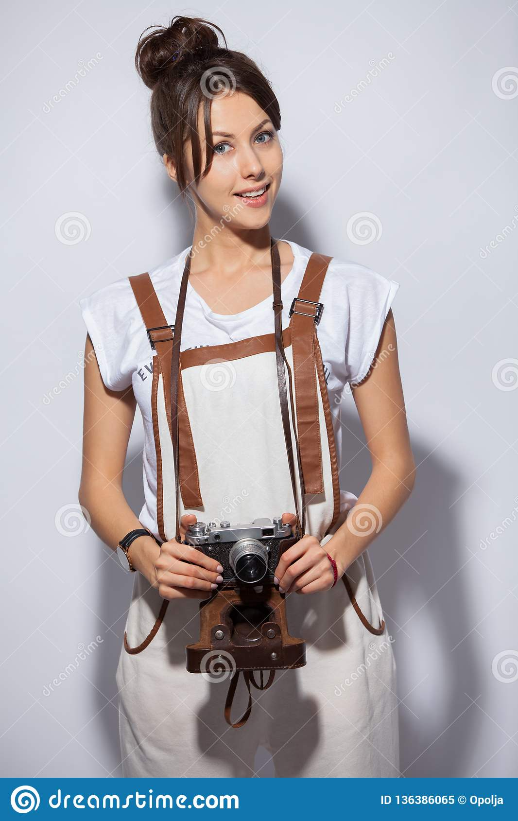 De jonge mooie camera van de vrouwenholding over witte achtergrond het bekijken camera