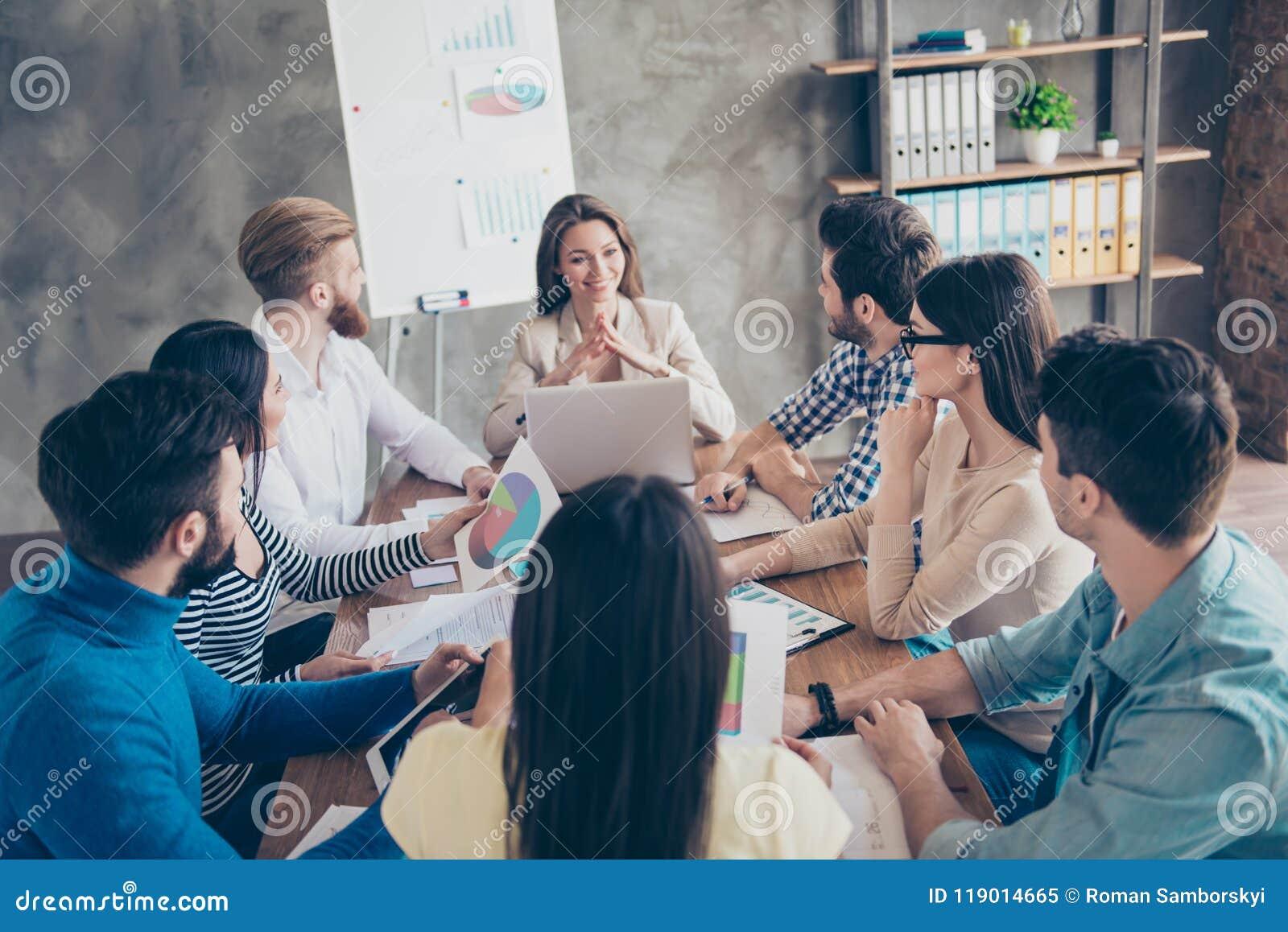 De jonge mooie dame rapporteert aan het team over developm