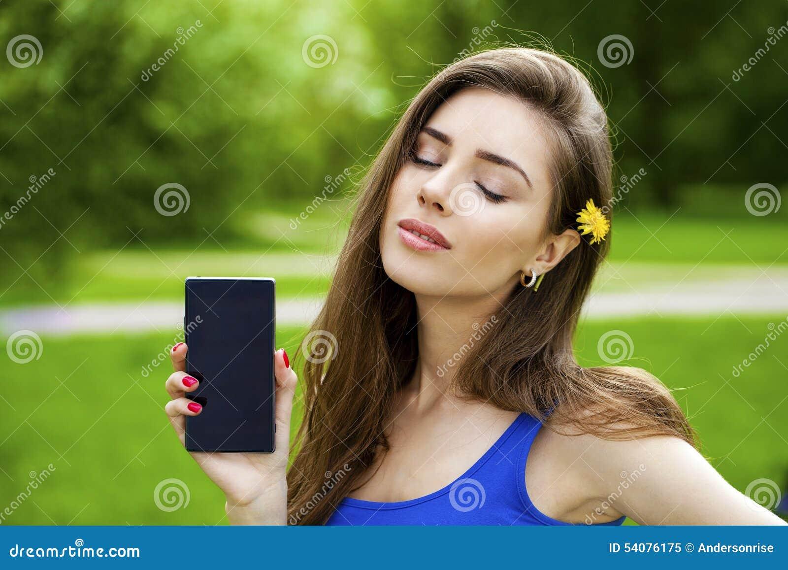 De jonge mooie donkerbruine vrouw toont een nieuwe slimme telefoon