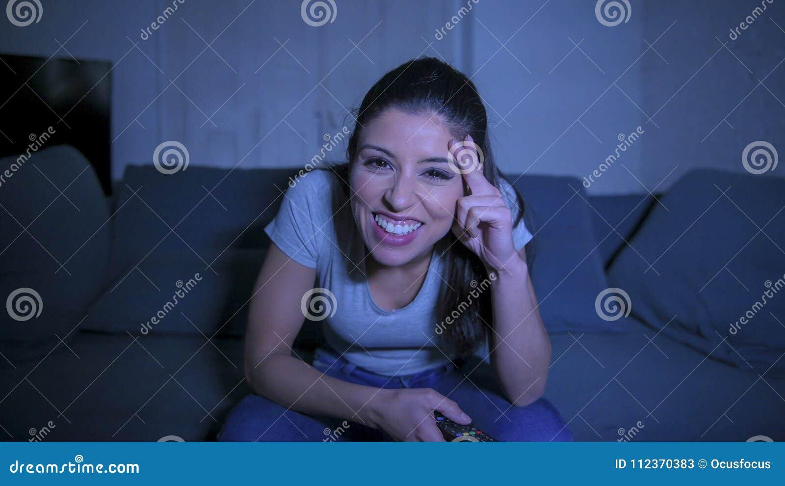 De jonge mooie en gelukkige Latijnse vrouw op haar jaren  30 die TV ver houden thuis genietend woonkamerlaag het letten op van te