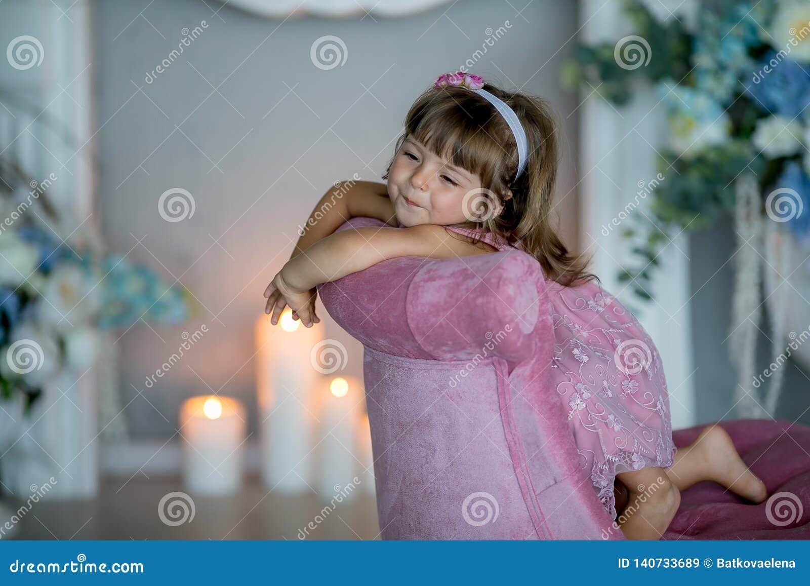 De jonge mooie meisjesballerina in een witte roze kleding bevindt zich in een witte ruimte dichtbij een witte lijst houdt een boe