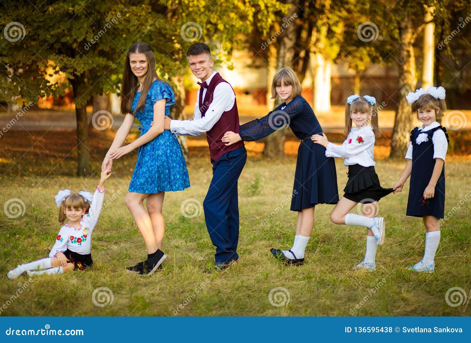 De jonge mooie moeder leidt vijf kinderen tot school Moeder van vele kinderen Grote familie gelukkig samen
