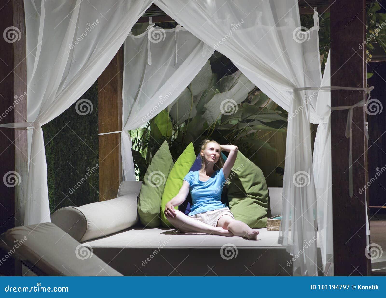 De jonge mooie vrouw heeft een rust bij warme tropische nacht op groot openluchtbed onder bedgordijnen met heldere kleurenhoofdku