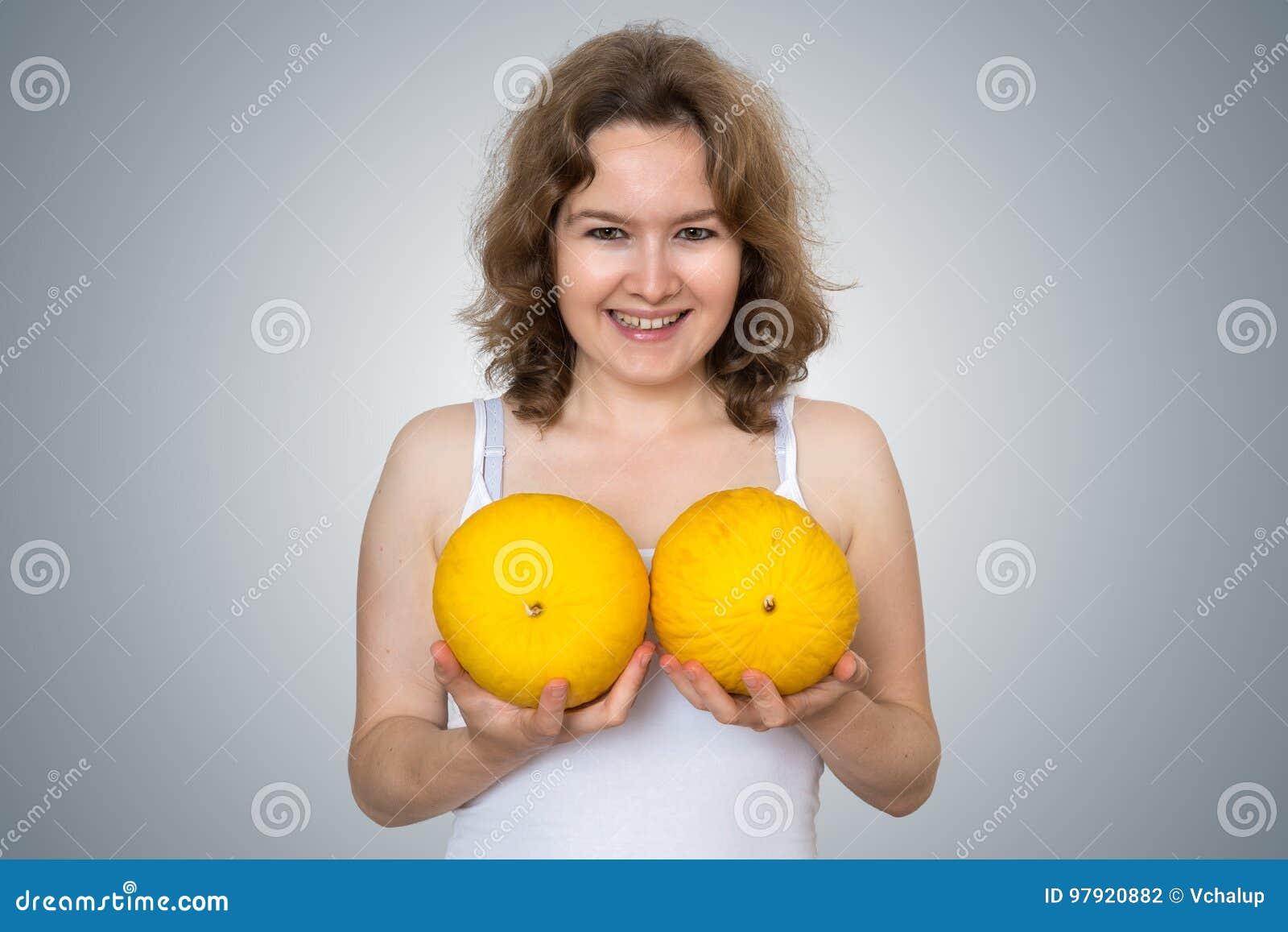 De jonge mooie vrouw houdt meloenen in handen boven haar borstplastische chirurgie en het silicone inplanteert concept