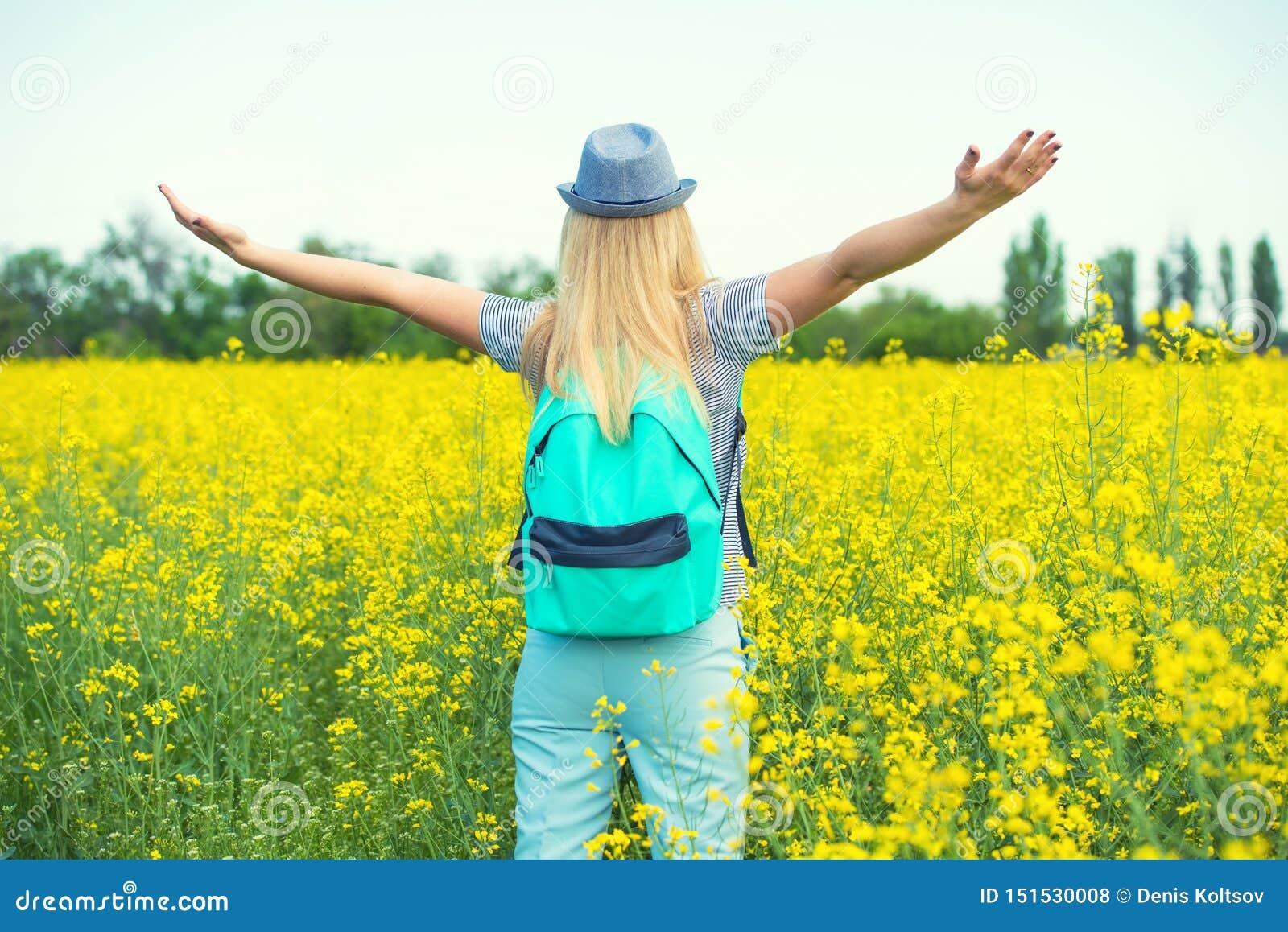 De jonge mooie vrouw loopt langs een bloeiend gebied op een zonnige dag