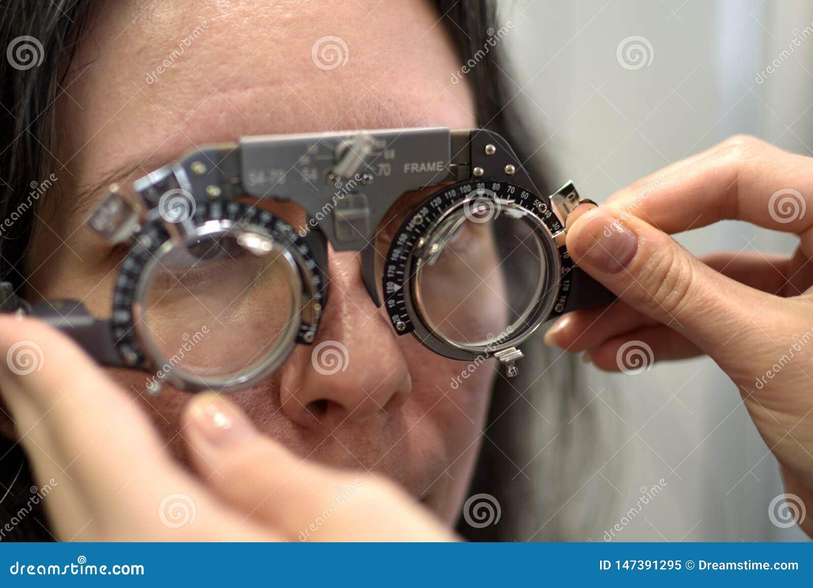 De jonge mooie vrouw ondergane procedure van de lensmontage in het uitstekende testende passende kader van de stijllens met oftal