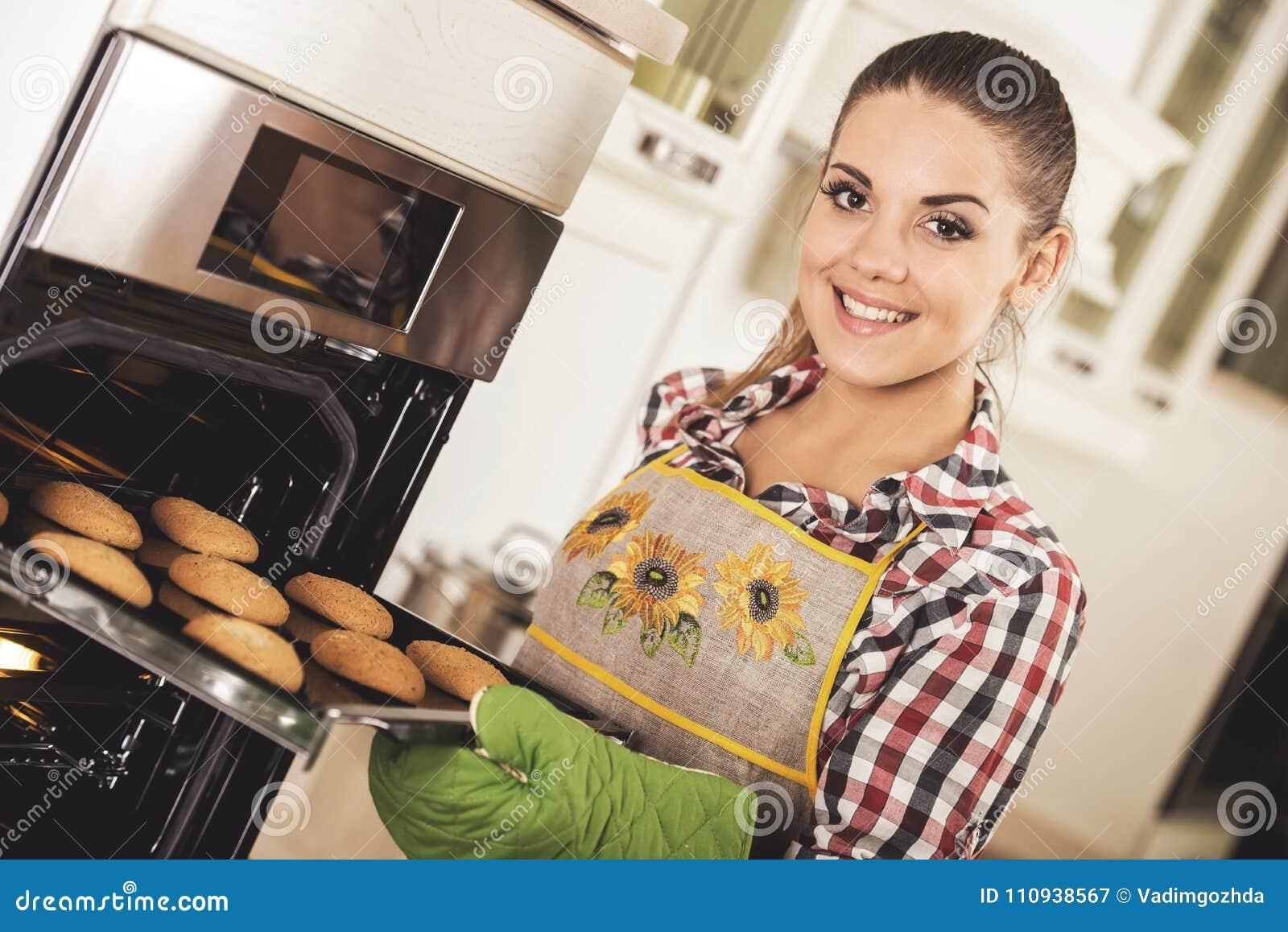 De jonge mooie vrouw trekt koekjes van de oven