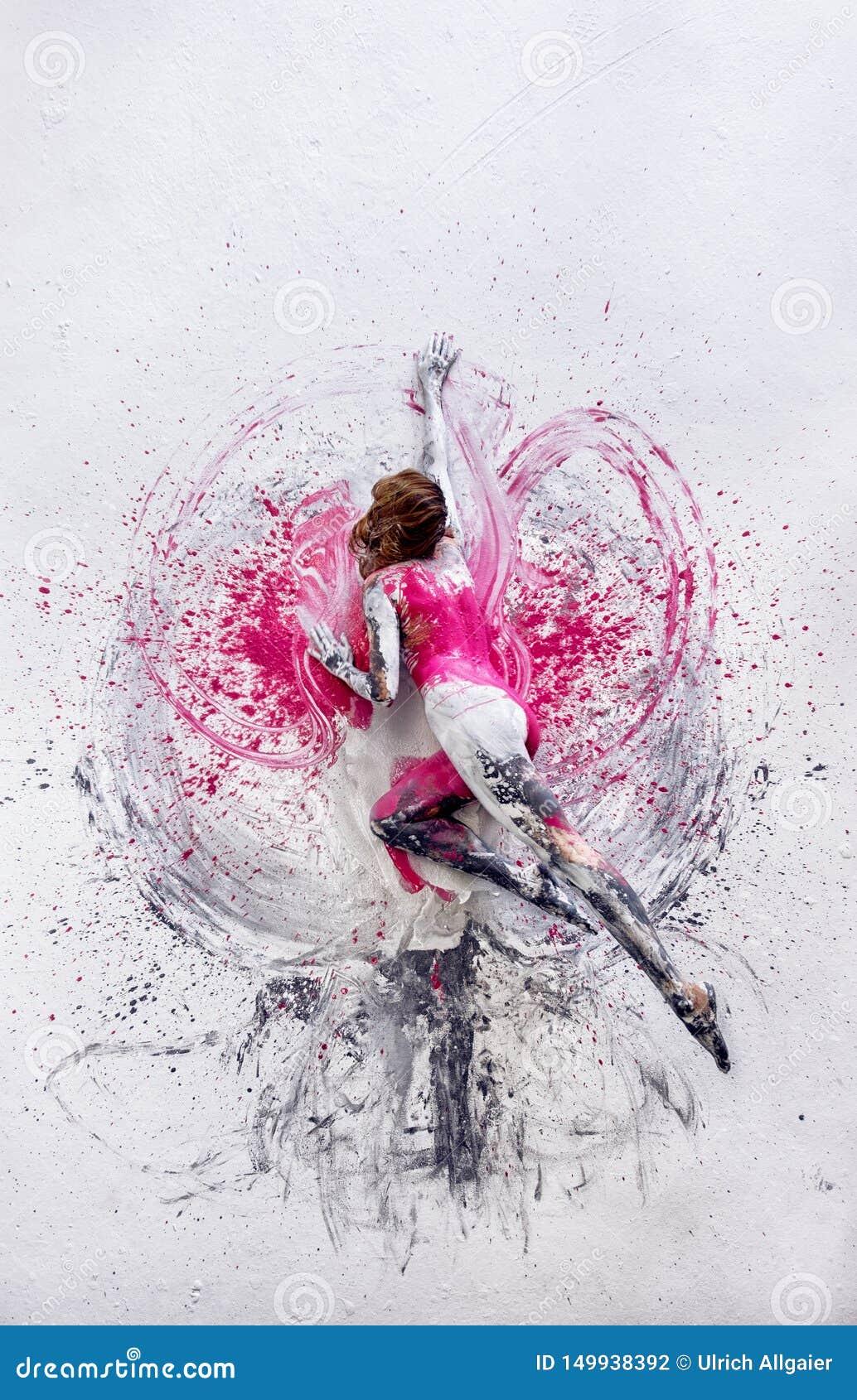 De jonge naakte vrouw in roze, grijs-witte, geschilderde kleur, ligt dansend op de elegant decoratieve vloer, in grijze en witte