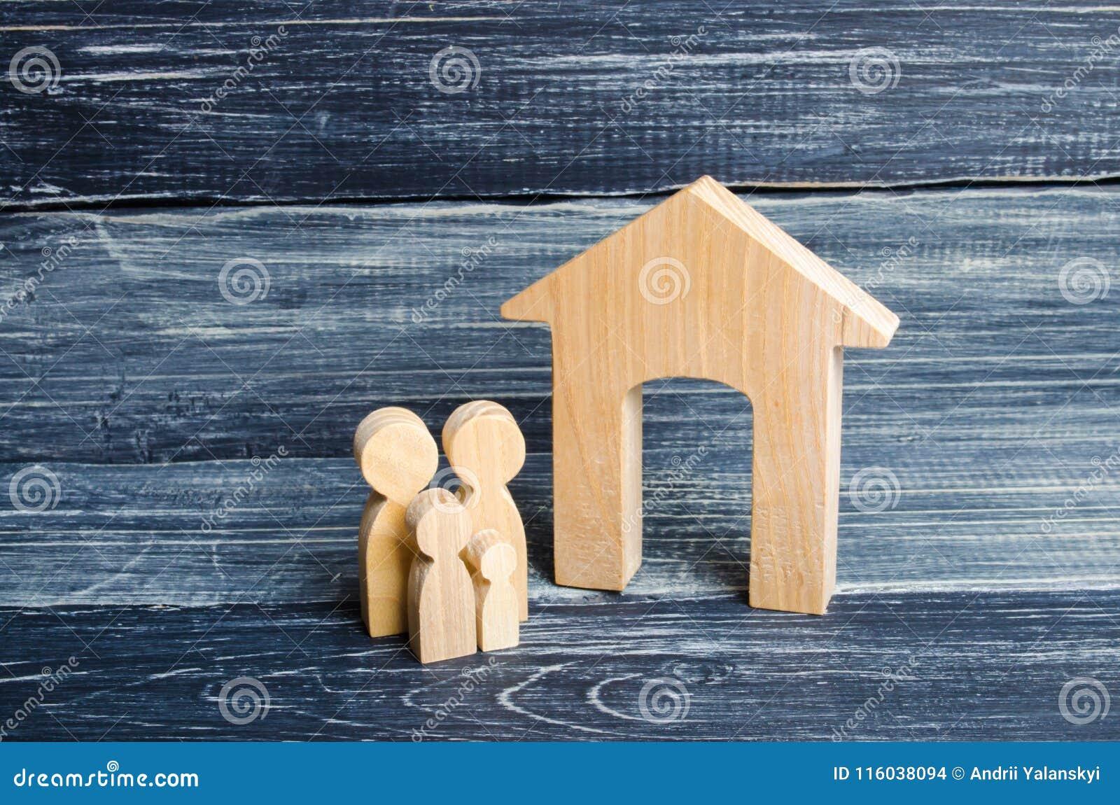 De jonge ouders en een kind bevinden zich dichtbij hun huis Concept die onroerende goederen, en een huis kopen verkopen Betaalbar