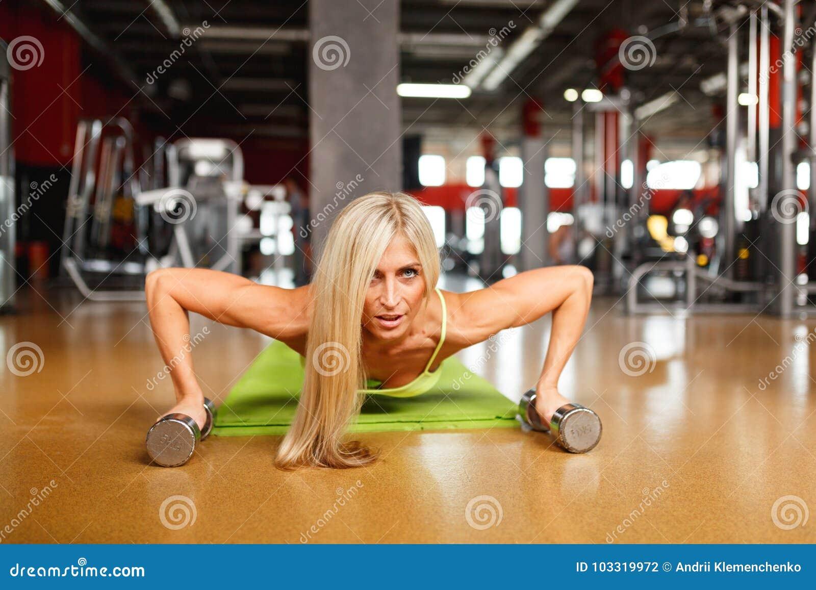 De jonge persen van het blondemeisje van de vloer met domoren Binnen, geschiktheidsclub