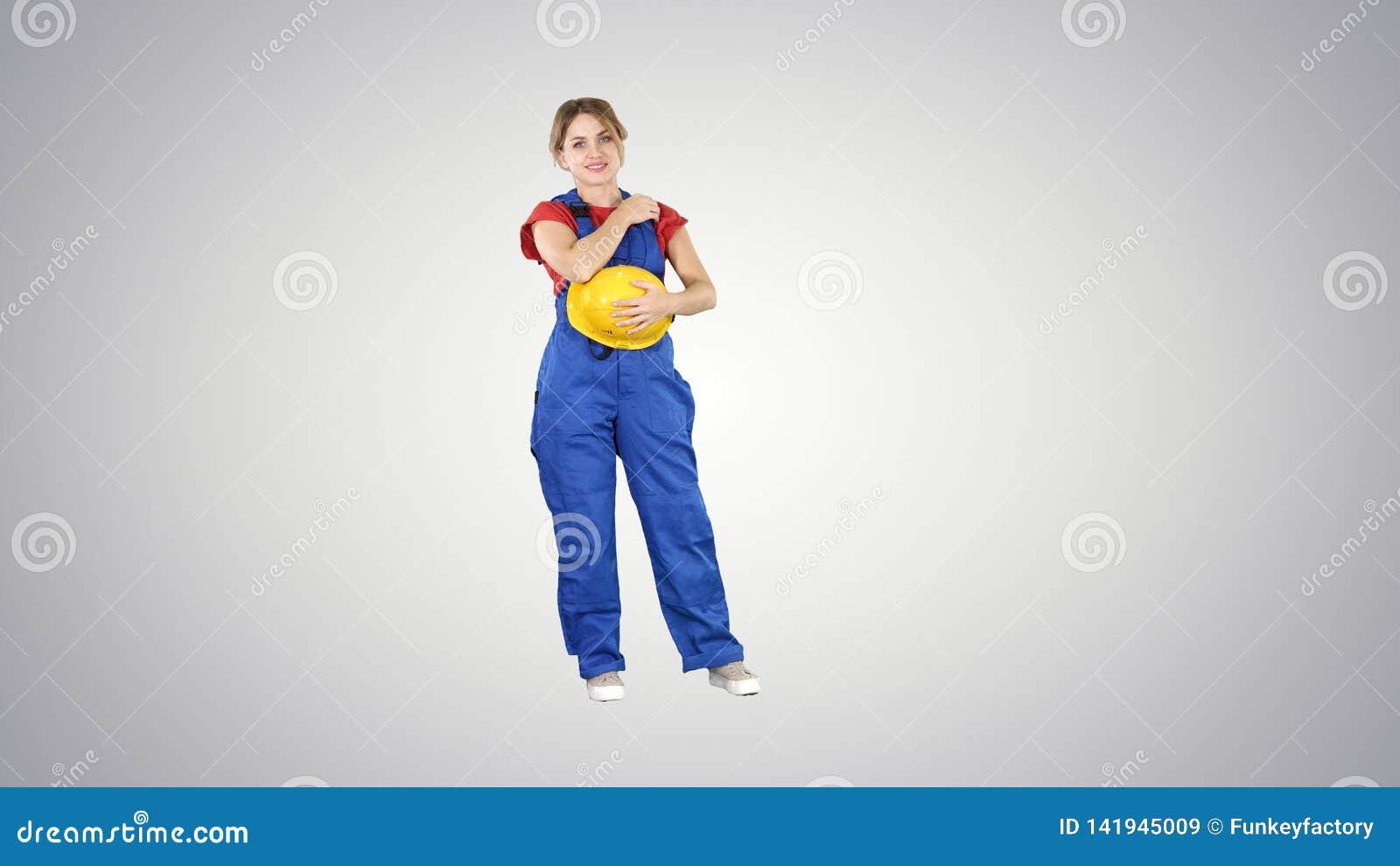 De jonge rode t-shirt van de vrouwenslijtage, met gele veiligheidshelm, ingenieur die op gradiëntachtergrond lachen