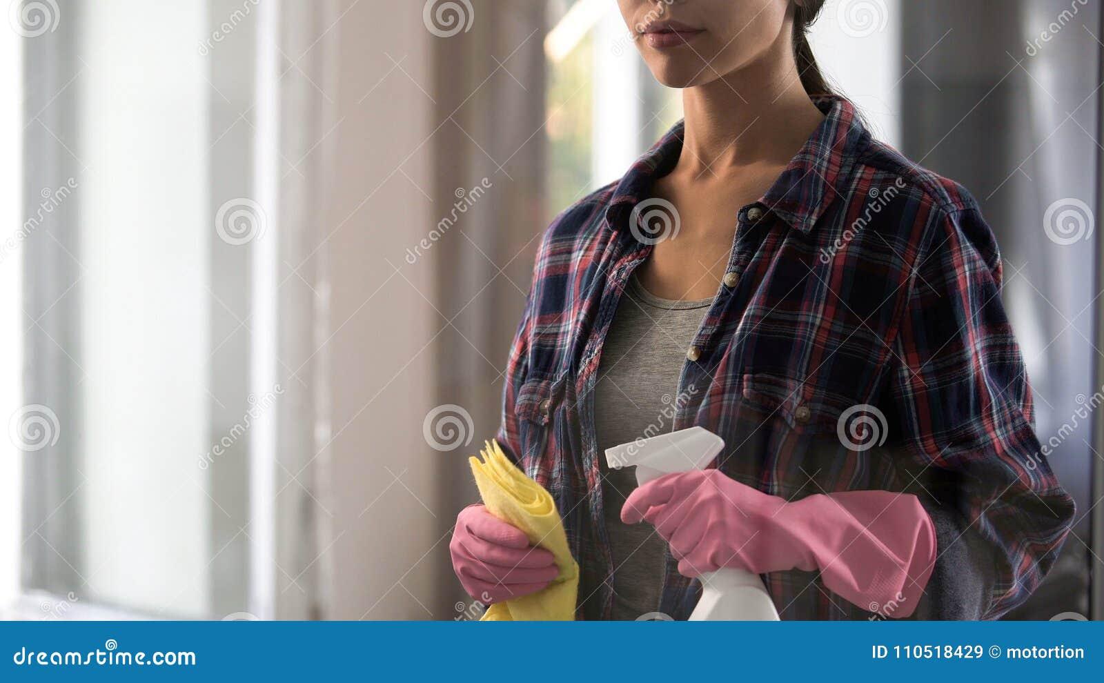 De jonge schoonmakende hulpmiddelen van de vrouwenholding in handen, atmosfeer versheid en comfort