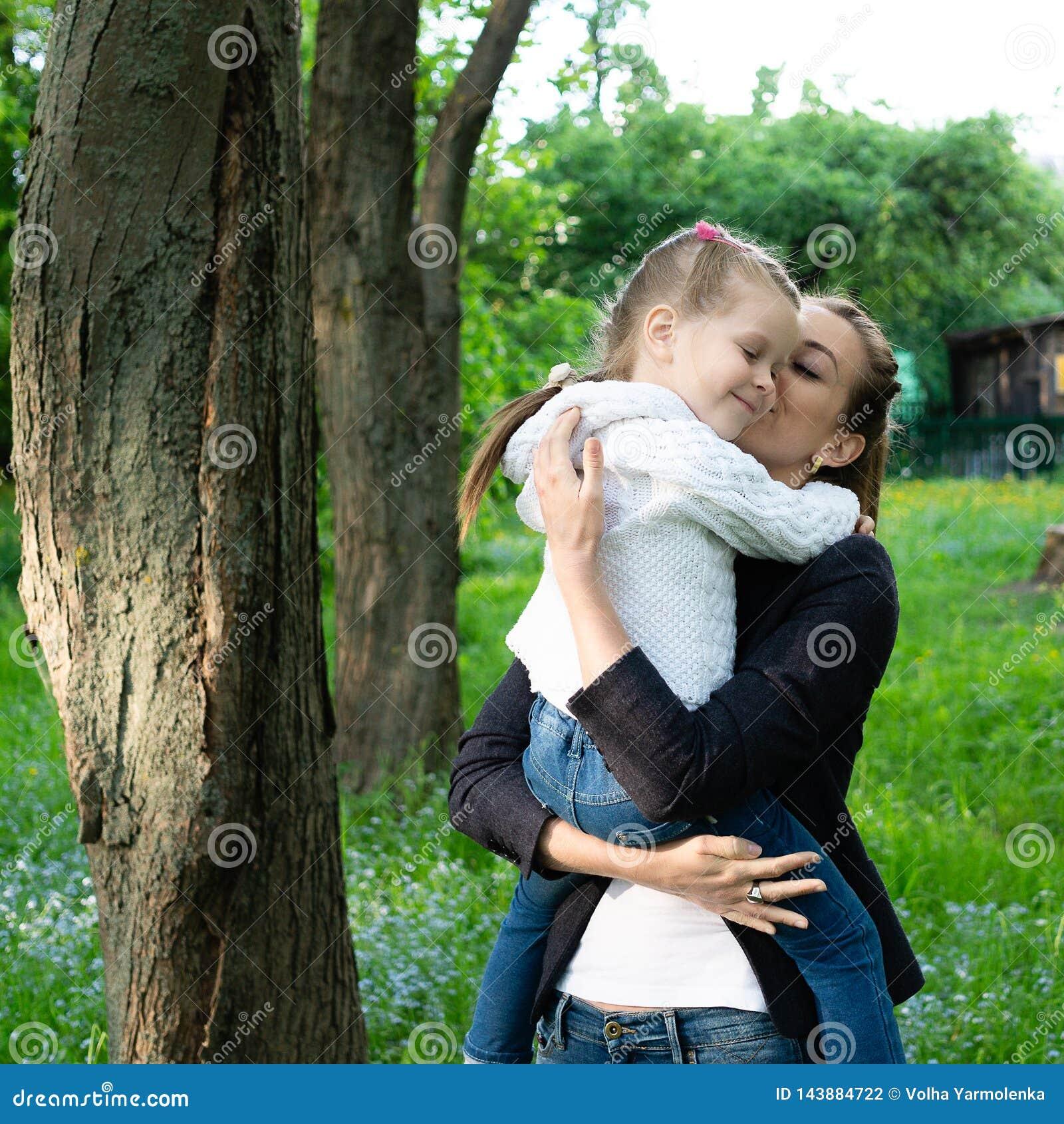 De jonge slanke moeder houdt in haar wapens en koestert een dochter