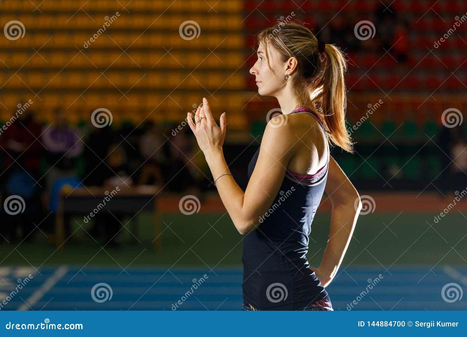 De jonge slanke poging van sportvrouw beginnende vérspringen