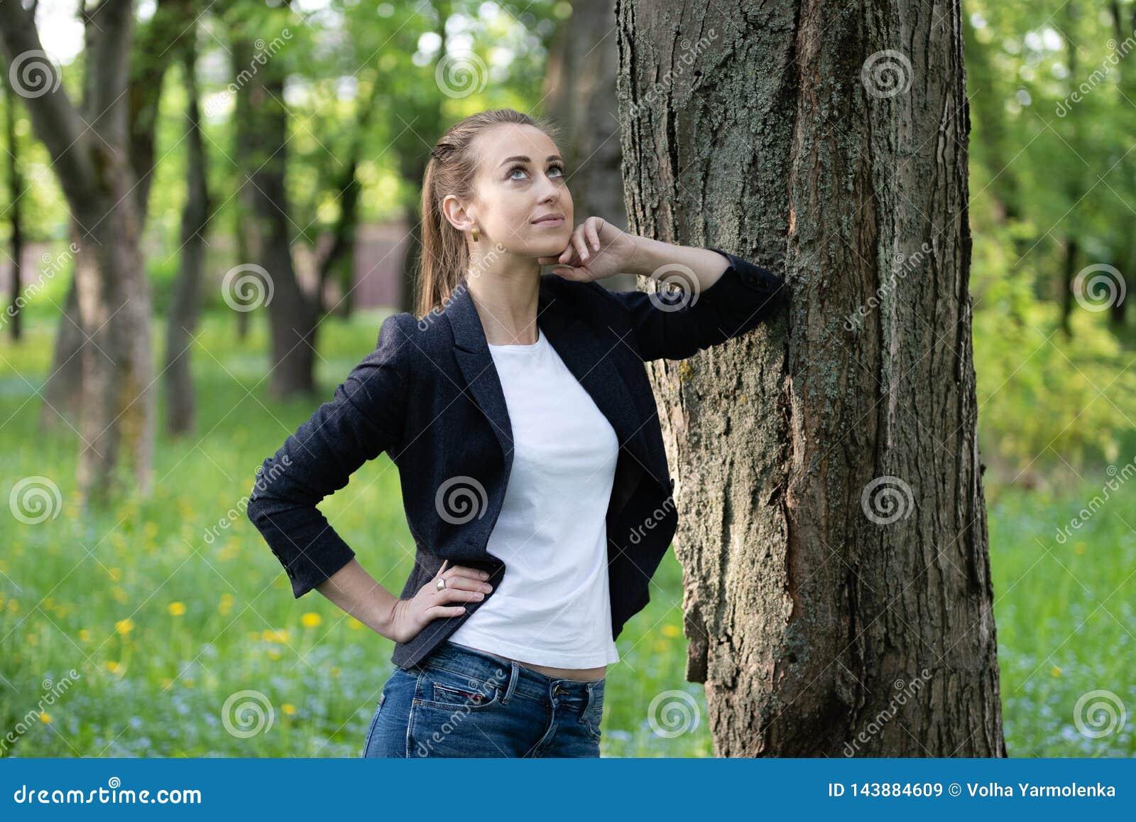 De jonge slanke vrouwenrust op een boomboomstam, op haar gezicht is een dromerige uitdrukking