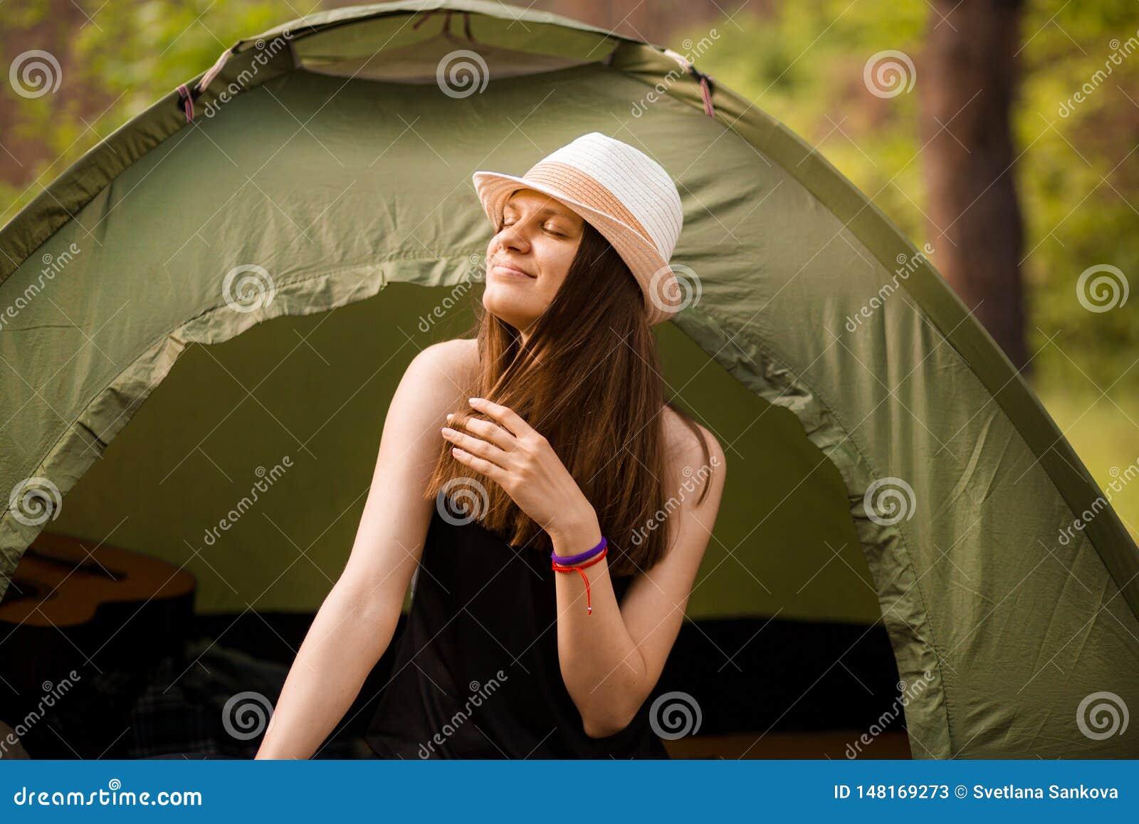 De jonge slanke zitting van de wandelaarvrouw bij kleine toeristentent die van mooi aardbos op heldere de zomerochtend genieten