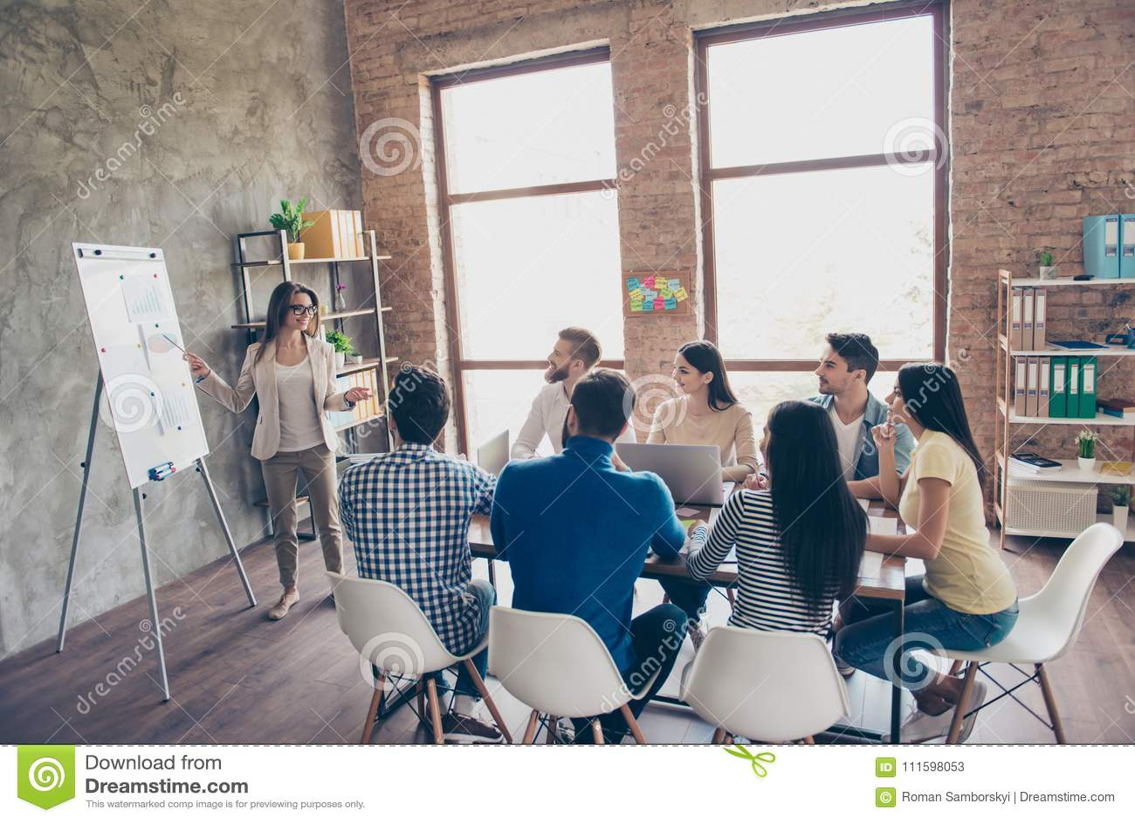 De jonge slimme dame in glazen rapporteert aan het team van collega s over het nieuwe project op de vergadering met de witte raad