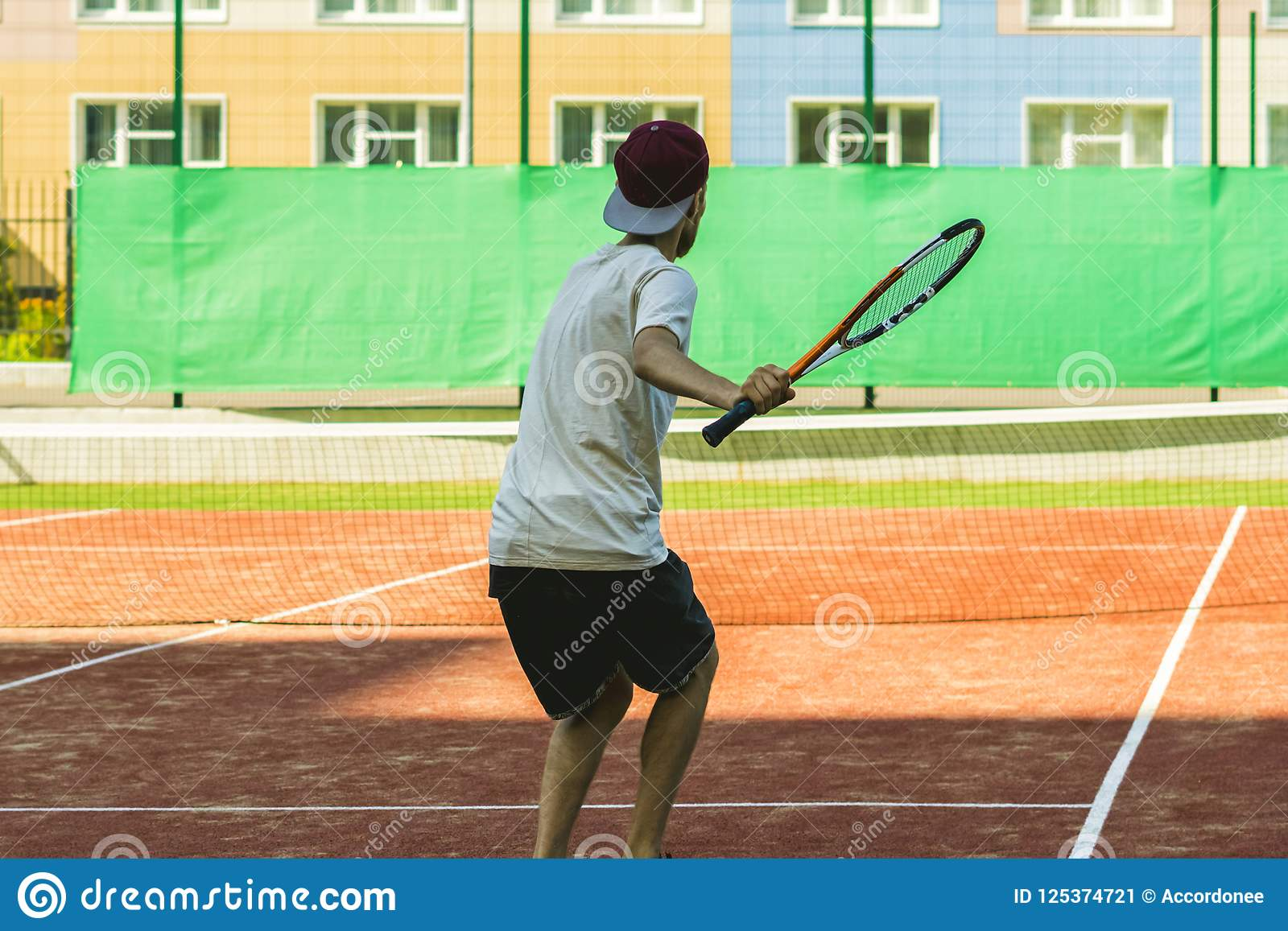 De jonge speler van het sport mannelijke tennis op de praktijk van het de zomerkamp