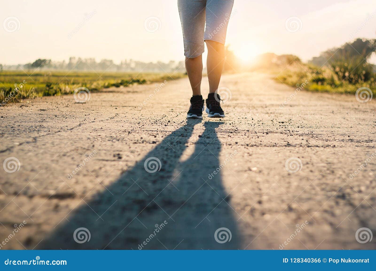 De jonge sportieve sleep die van de geschiktheidsvrouw op landelijke weg in de zomer lopen