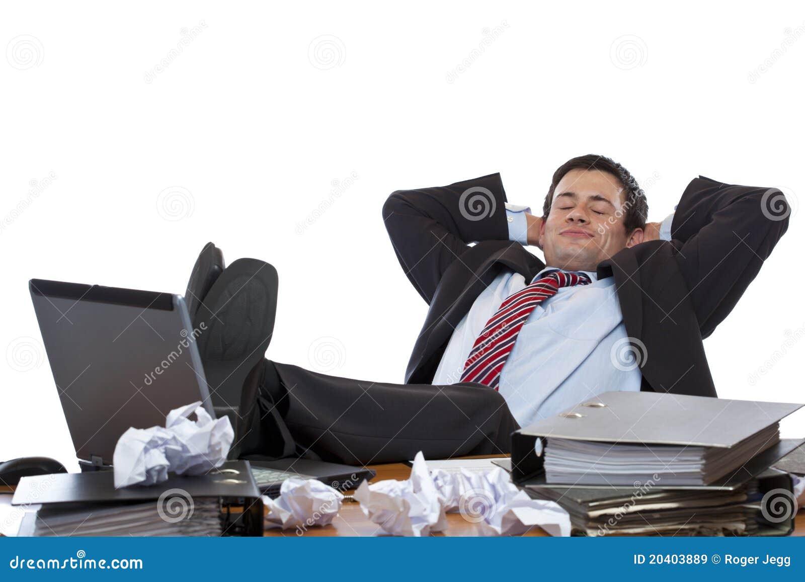 De jonge stafmedewerker ontspant met voeten bij bureau