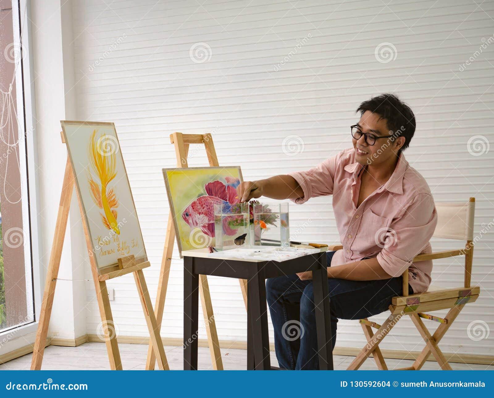 De jonge volwassen Mannelijke waterverfkunstenaar Feeding de vissen terwijl het trekken van de vissen schildert,