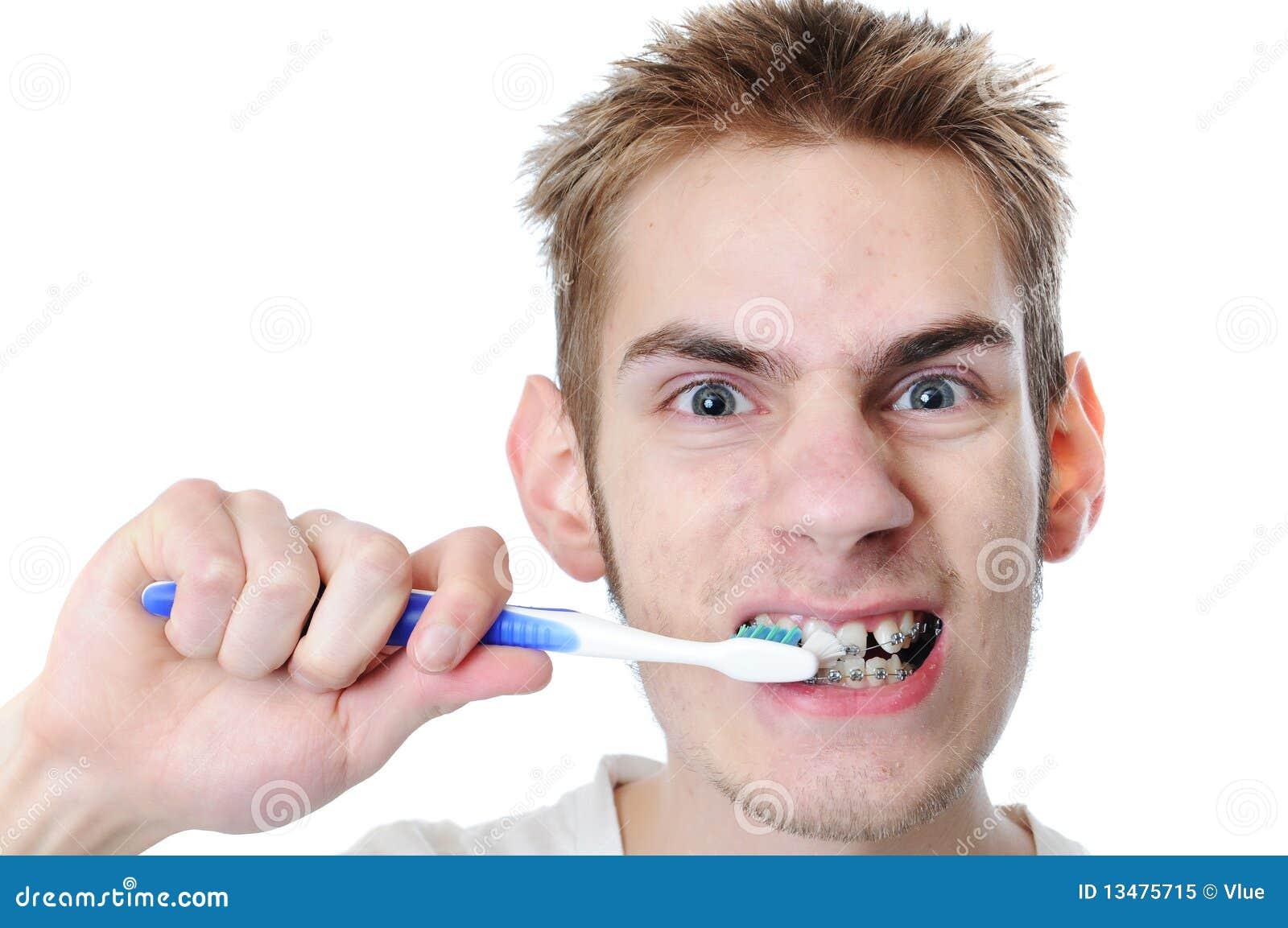 De jonge volwassen mens borstelt tanden