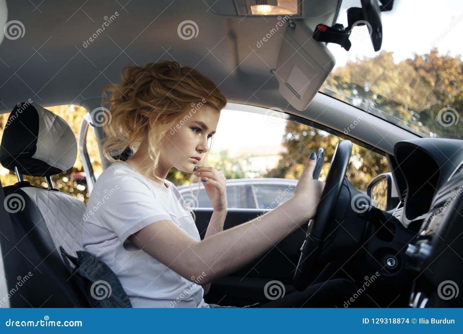 De jonge vrouw bekijkt haar smartphone in een auto Gestemd beeld