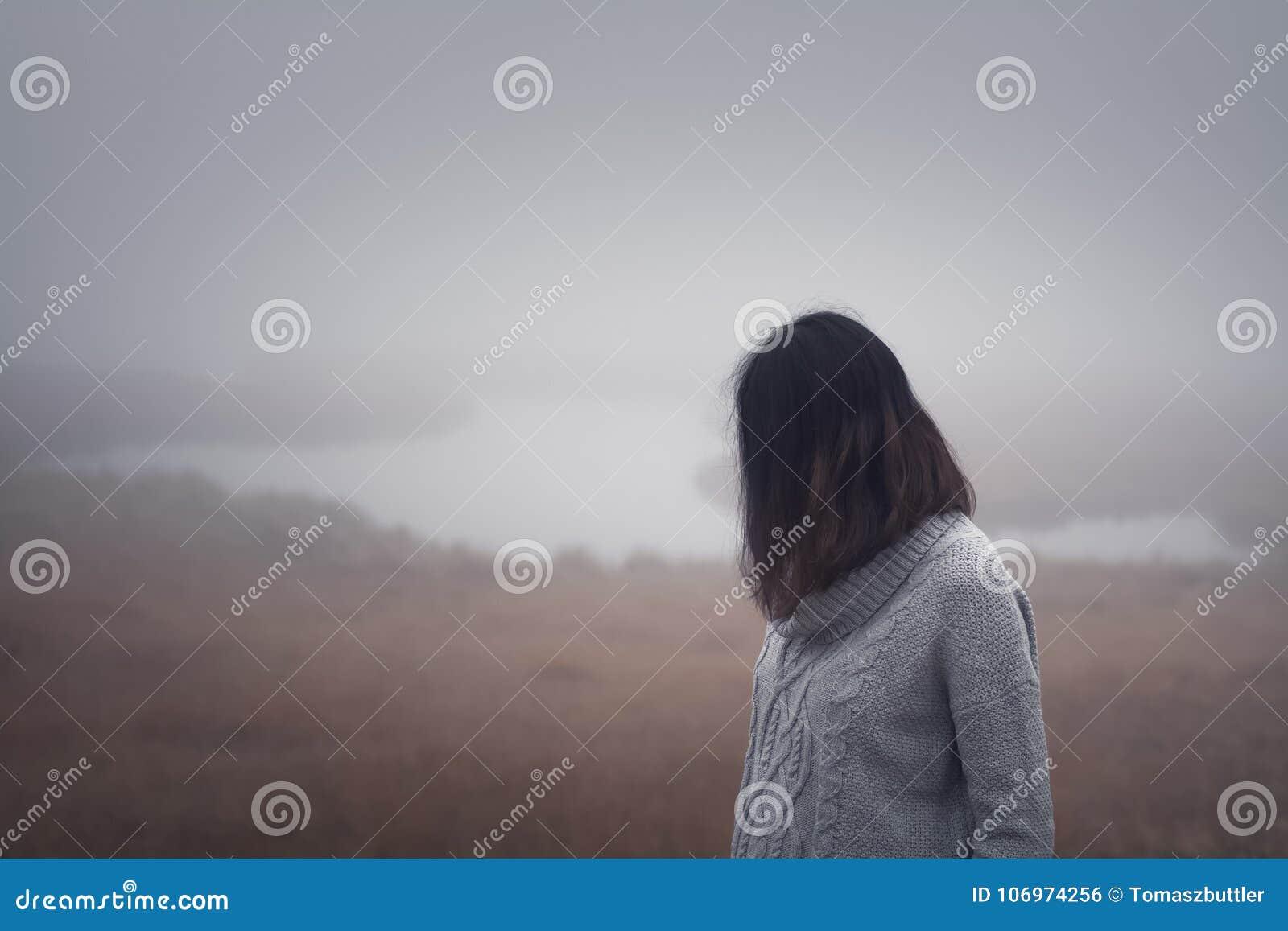 De jonge vrouw bevindt zich door het water in de mist op een mistige dag