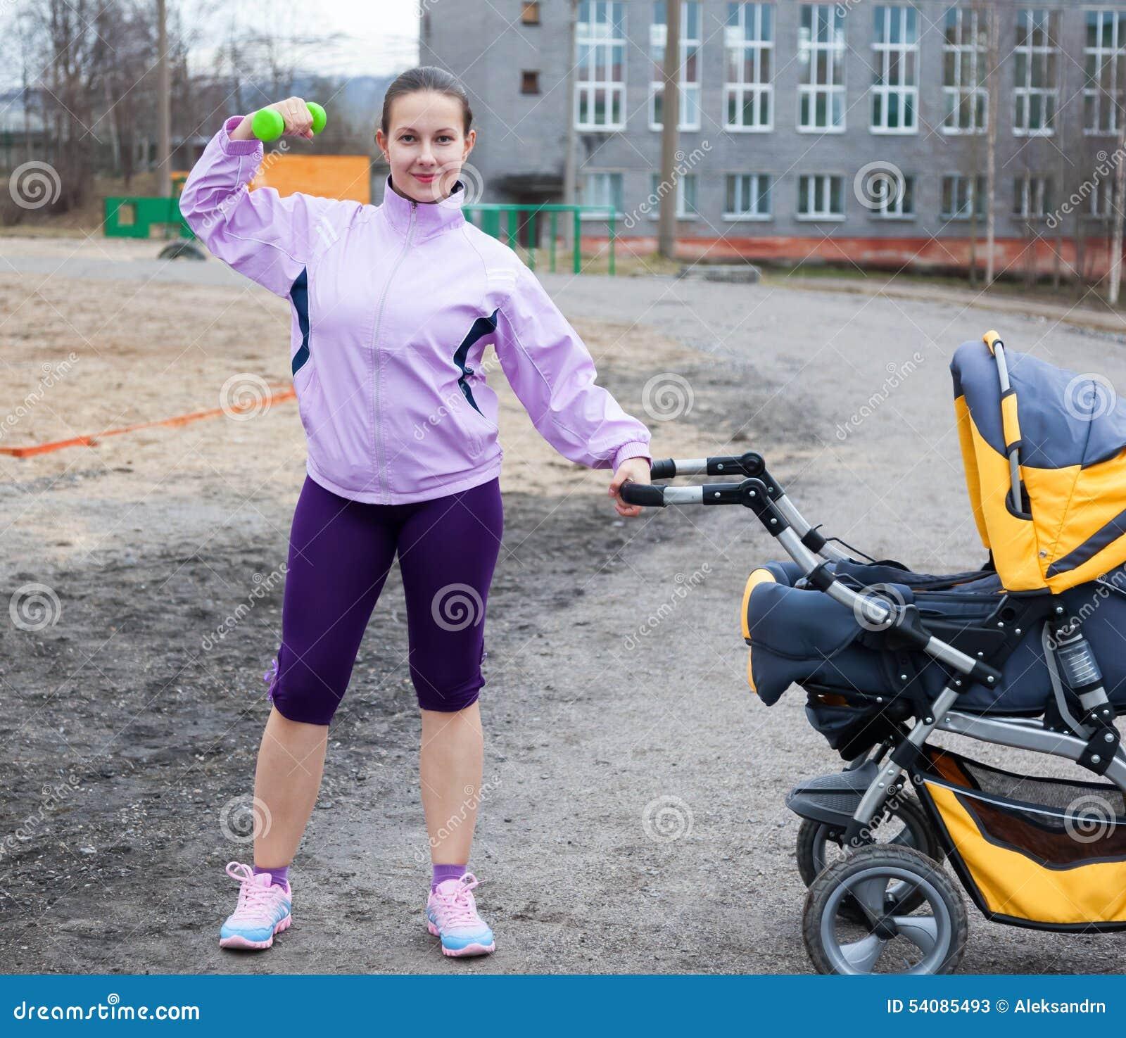 De jonge vrouw combineert sport en een gang met baby